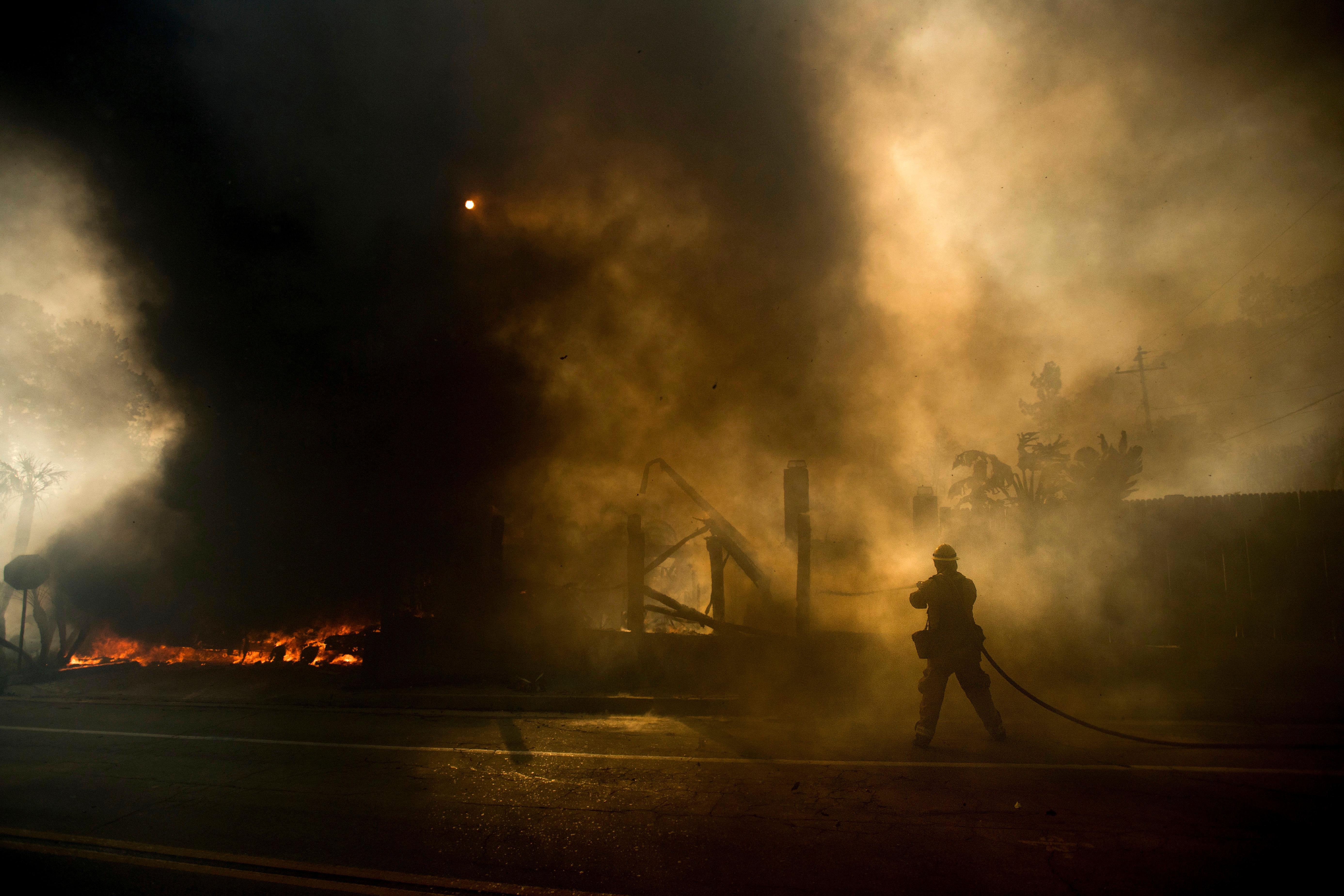 A firefighter tries to keep flames from spreading while battling a wildfire in Ventura, Calif., on Tuesday, Dec. 5, 2017. (AP Photo/Noah Berger)