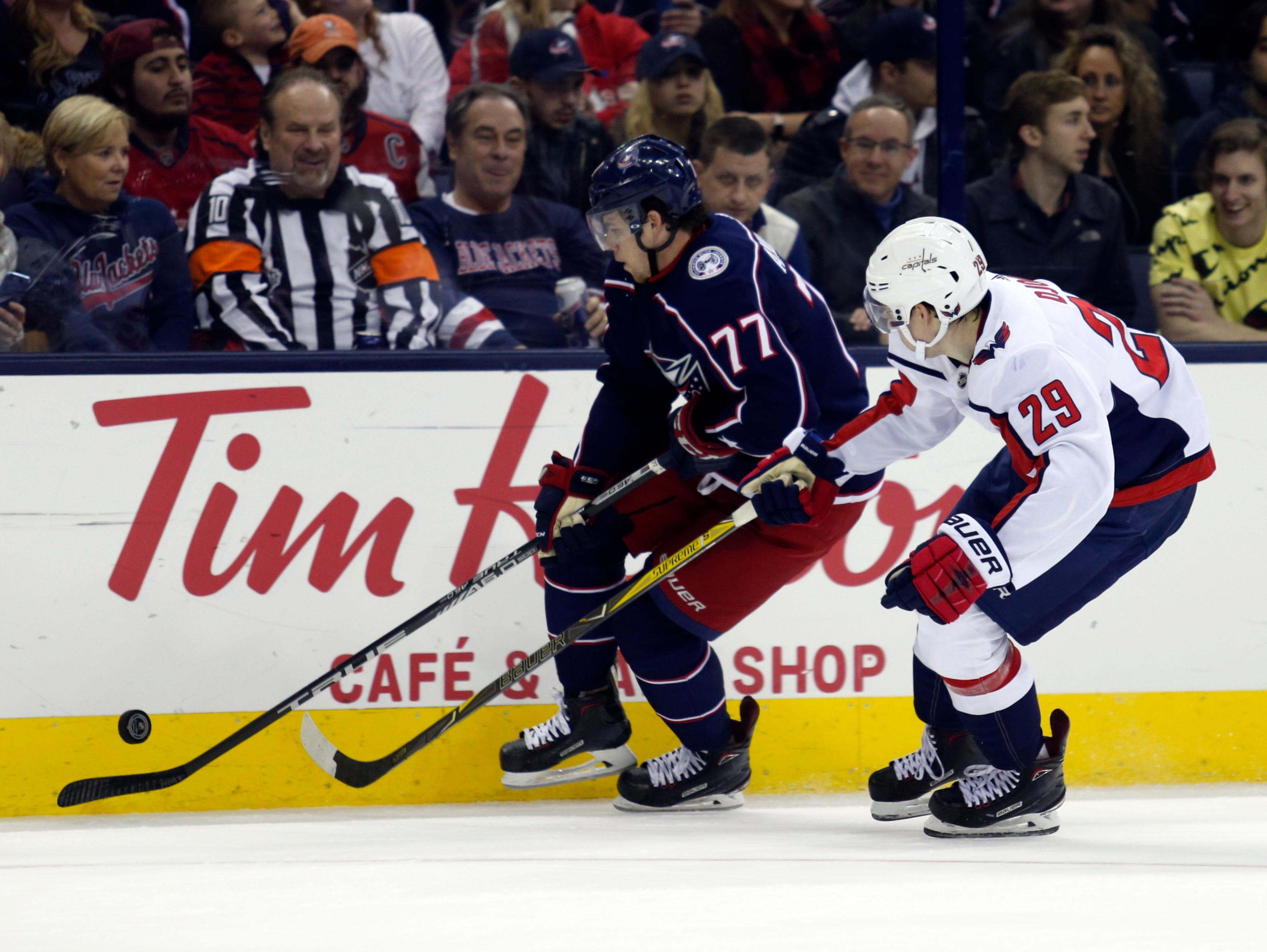 Columbus Blue Jackets forward Josh Anderson, left, chases the puck against Washington Capitals defenseman Christian Djoos, of Sweden, during the second period of an NHL hockey game in Columbus, Ohio, Monday, Feb. 26, 2018. (AP Photo/Paul Vernon)