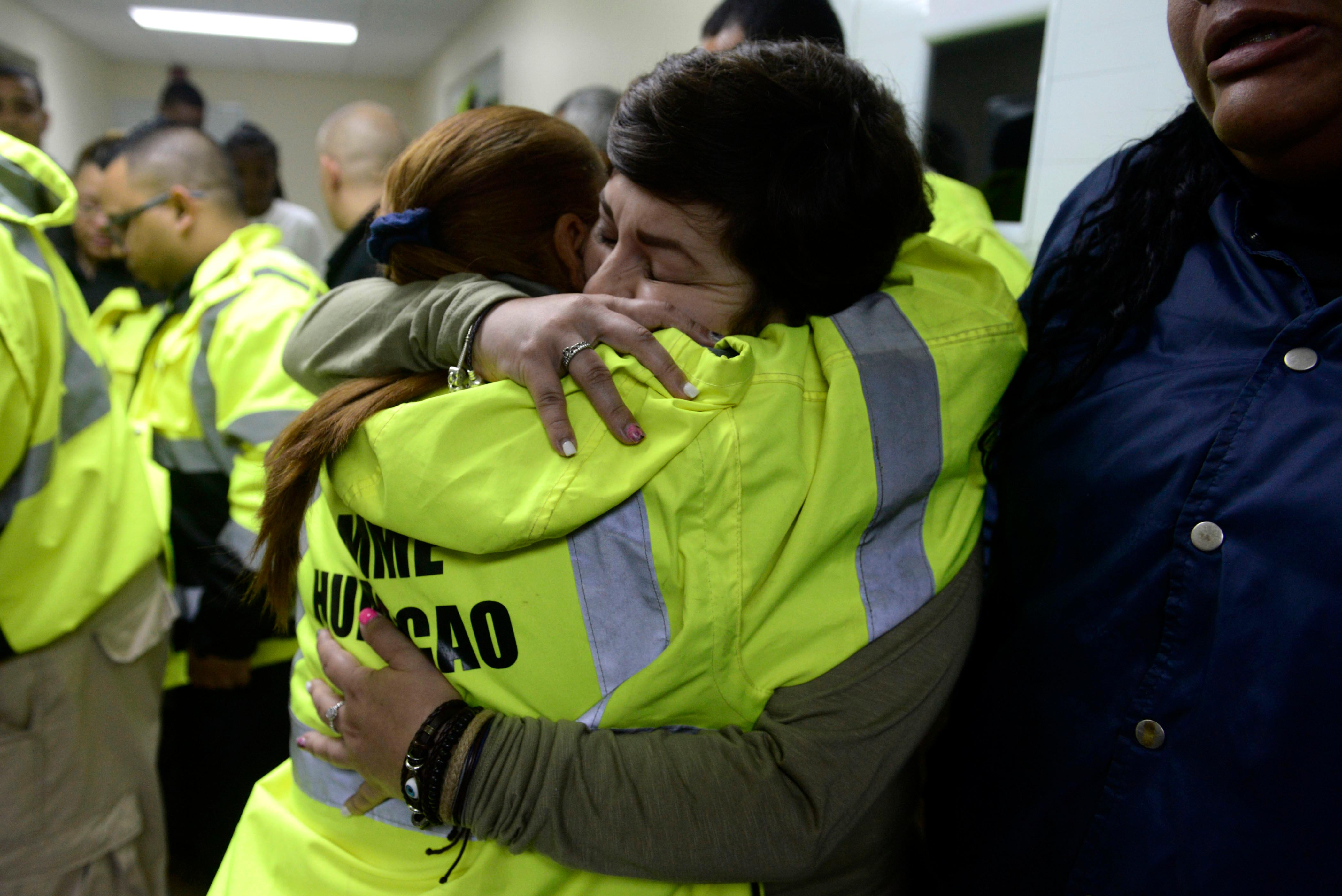 Rescue team members Candida Lozada, left, and Stephanie Rivera, right, embrace as they wait to assist in the aftermath of Hurricane Maria in Humacao, Puerto Rico, Wednesday, Sept. 20, 2017. (AP Photo/Carlos Giusti)