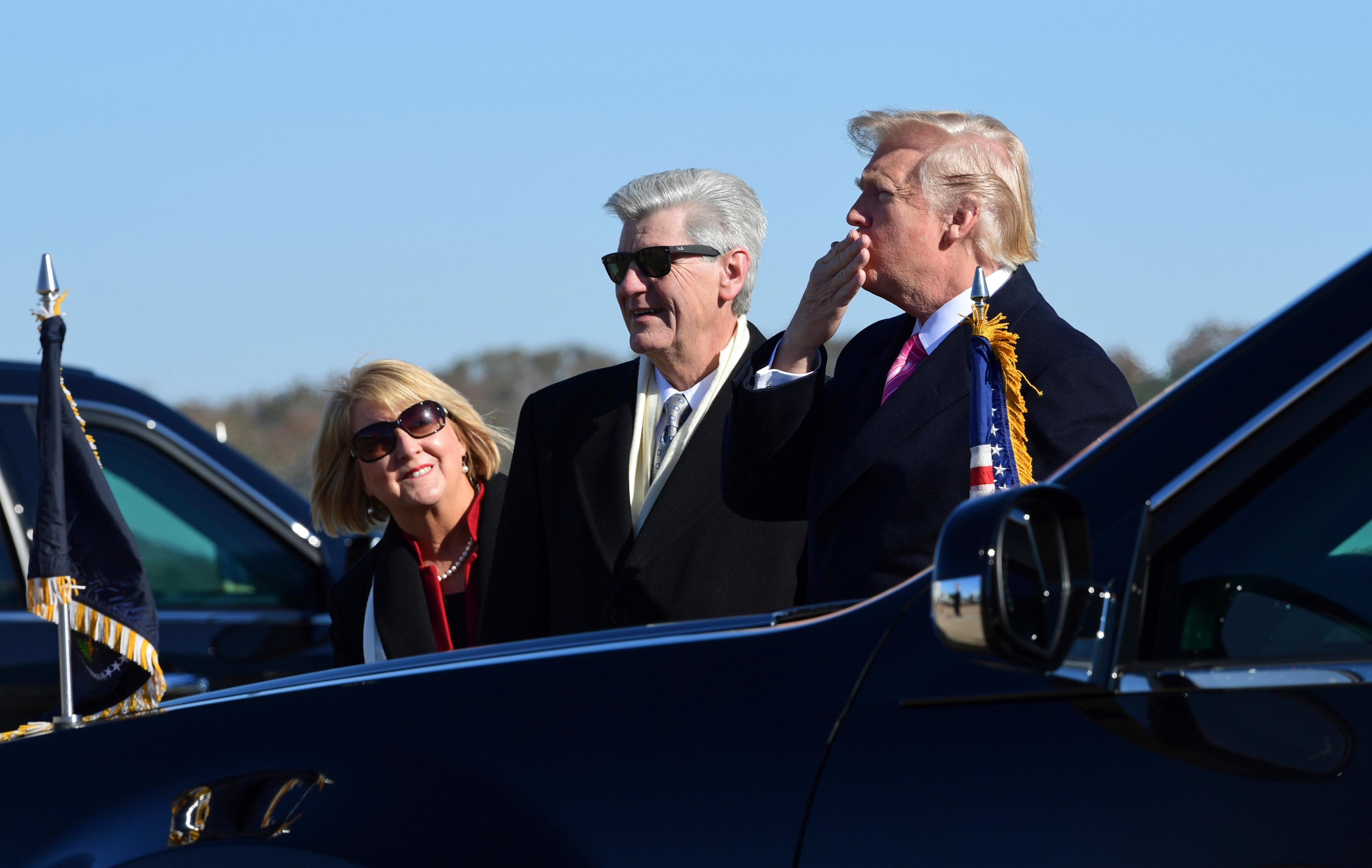 President Donald Trump, right, standing with Mississippi Gov. Phil Bryant, center, blows a kiss to the crowd after arriving on Air Force One at Jackson-Medgar Wiley Evers International Airport in Jackson, Miss., Saturday, Dec. 9, 2017.{&amp;nbsp;} (AP Photo/Susan Walsh)<p></p>