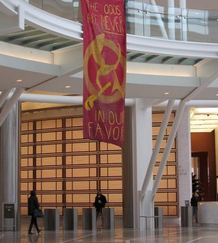 Protesters fly a banner similar to the Hunger Games. It reads 'The Odds are never in our favor'