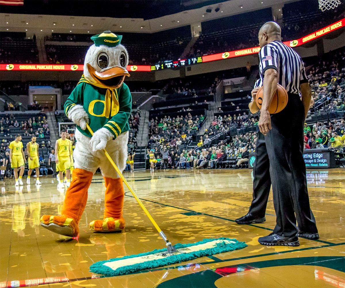 The Oregon Duck helps with sweeping the floor around the referees. The Oregon Ducks defeated Texas Southern Tigers 74-68. The Ducks are now 7-3 overall in the Pac-12. Photo by August Frank. Oregon News Lab