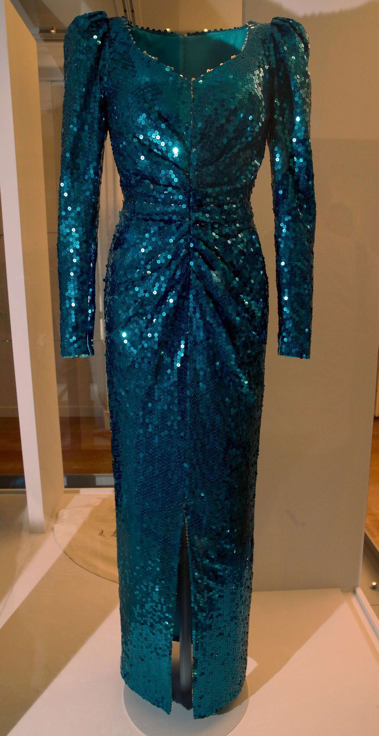 "An evening dress by Catherine Walker of green sequins and worn by Diana, Princess of Wales on an official visit to Austria 1986and two other events on display during a media preview of an exhibition of 25 dresses and outfits worn by Diana entitled ""Diana: Her Fashion Story"" at Kensington Palace in London, Wednesday, Feb. 22, 2017. (AP Photo/Alastair Grant)"