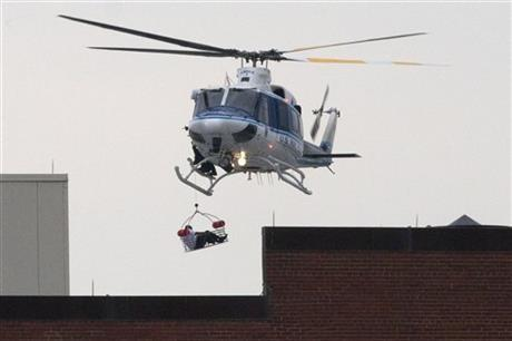 A U.S. Park Police helicopter removes a man in a basket from the Washington Navy Yard. The exact number of people killed and the conditions of those wounded was not immediately known.