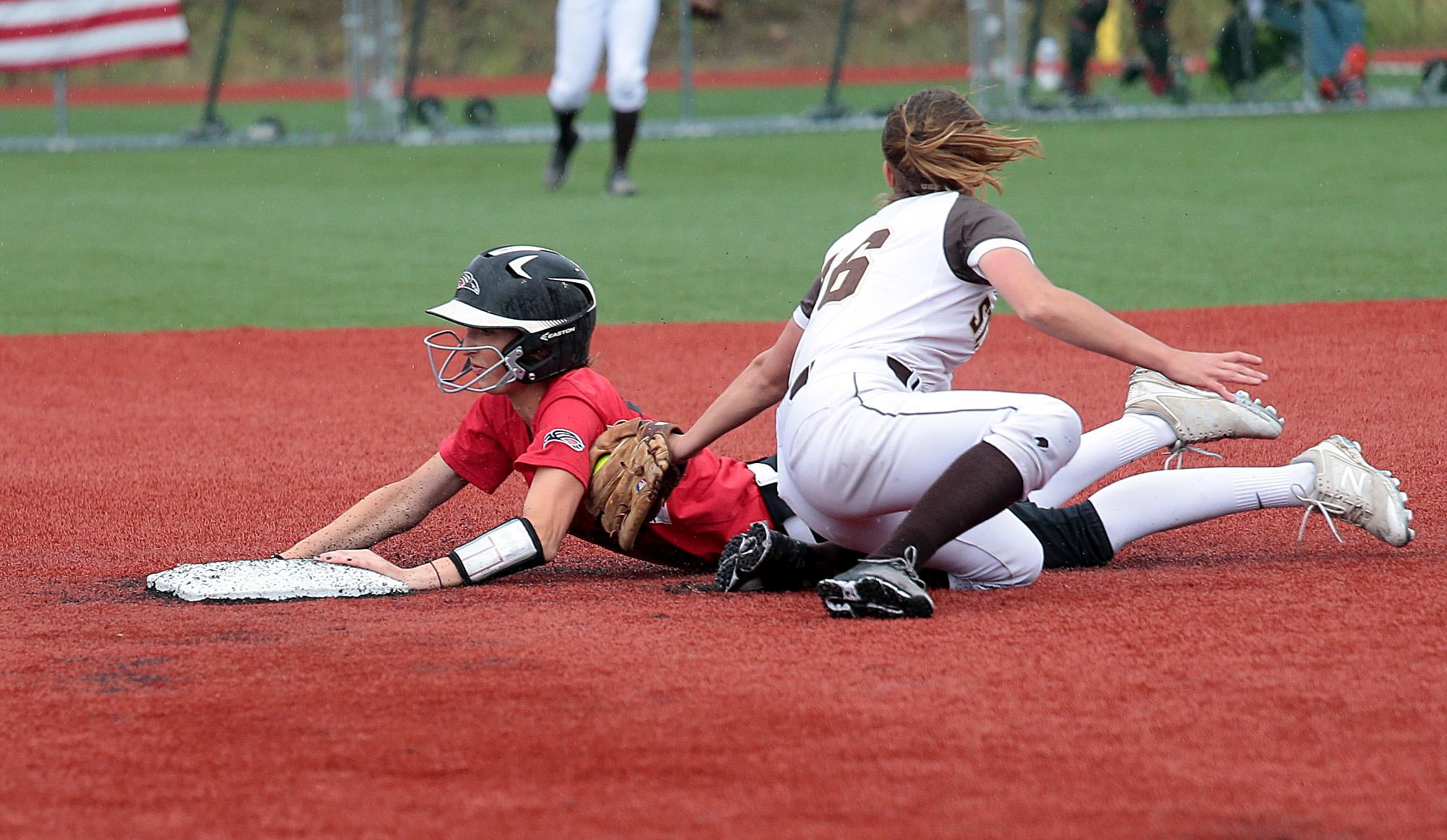 Larry Stauth Jr./For the Daily TidingsSouthern Oregon University freshman Hannah Shimek slides in under the tag by St. Francis shortstop Ashley Galason at U.S. Cellular Community Park on Wednesday.