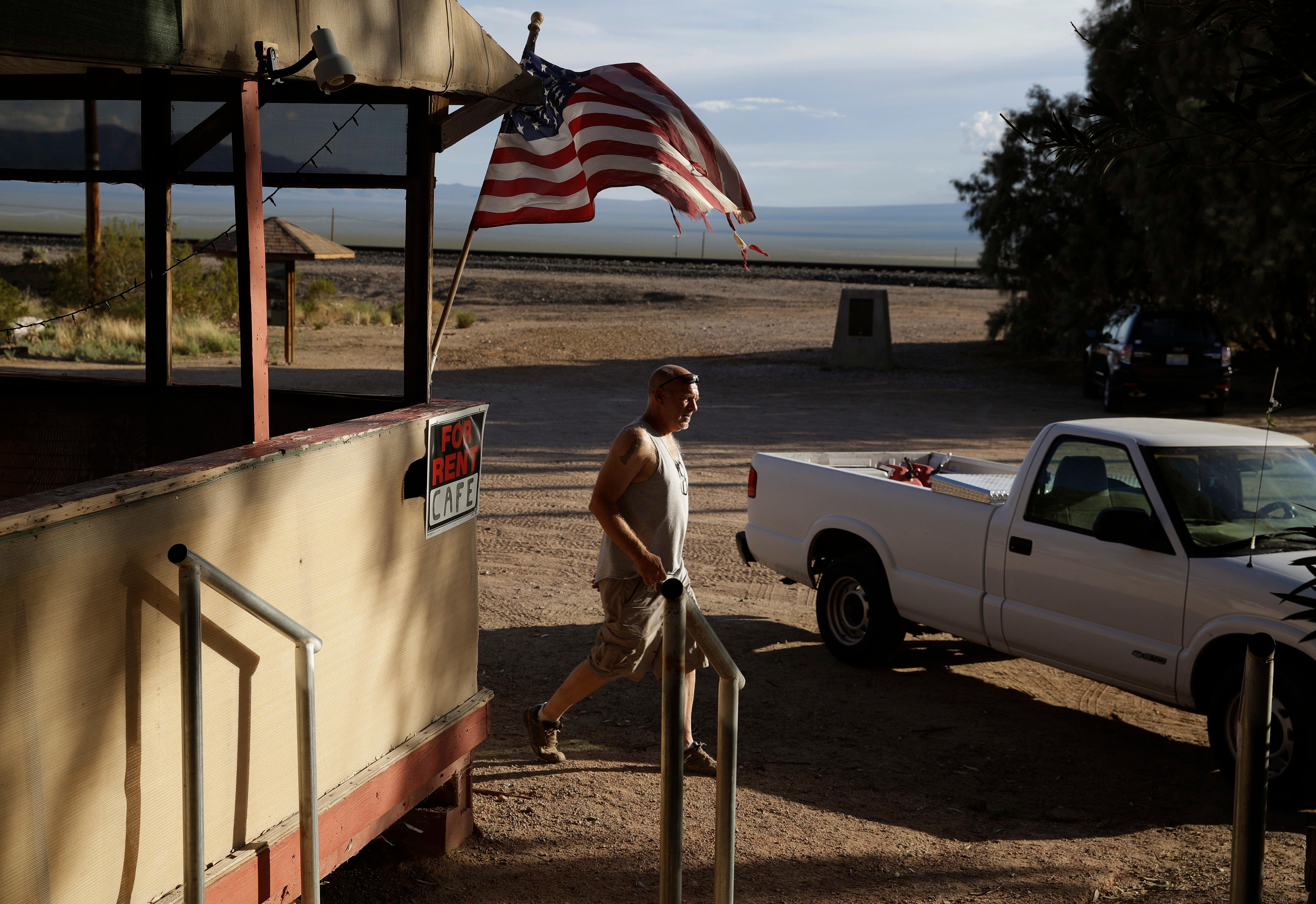 Carl Cavaness walks to the Nipton Trading Post, Thursday, Aug. 3, 2017, in Nipton, Calif. American Green Inc., one of the nation's largest cannabis companies, announced it has bought the entire 80 acre California desert town of Nipton. (AP Photo/John Locher)