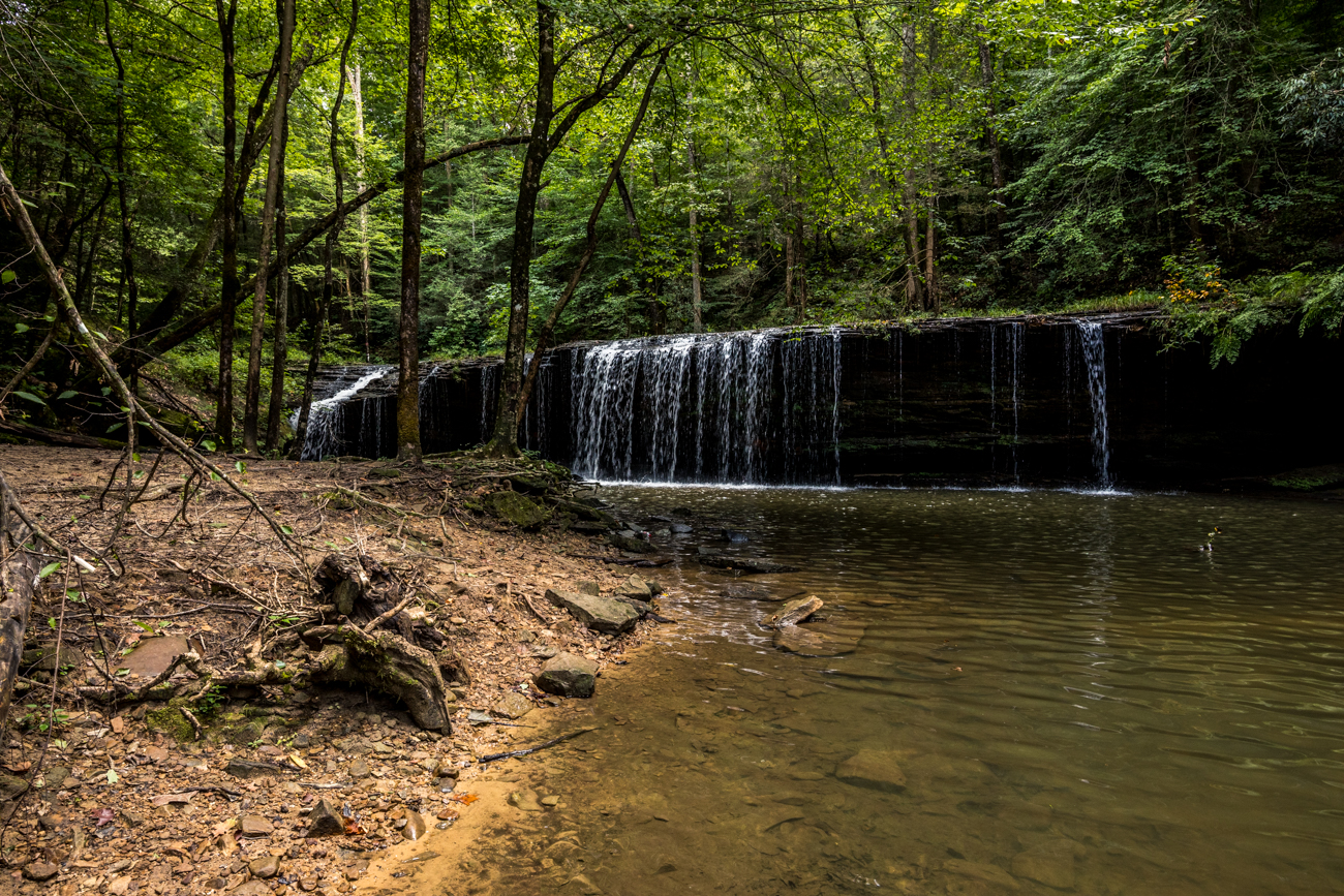Stop #2: Princess Falls / ADDRESS: 979 KY-92, Stearns, KY (42647) / Head about an hour east to find the next stop, Princess Falls. Follow the address to a gravel parking area. There is a two-and-a-half-mile trail with an elevation gain of 95 feet that highlights Princess Falls as well as a waterfall called Julia Lynn Falls. The trail leads you along the Lick Creek and runs parallel with the Cumberland River. You'll also get to hike a section of Sheltowee Trace, which is known for its lengths along the Appalachian Trail. The falls themselves make for an excellent swimming hole with clear, cold water. / Image: Catherine Viox // Published: 9.28.20