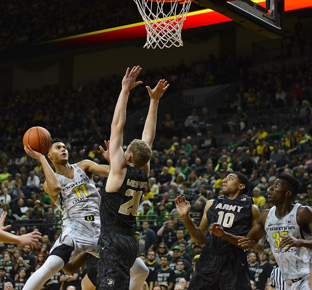 Army's Mac Hoffman (#20) unsuccessfully attempts to block Ducks' Keith Smith's (#11) shot. In front of a sold out crowd, Oregon defeated Army 91-77 on opening night. Photo by Jacob Smith, Oregon News Lab