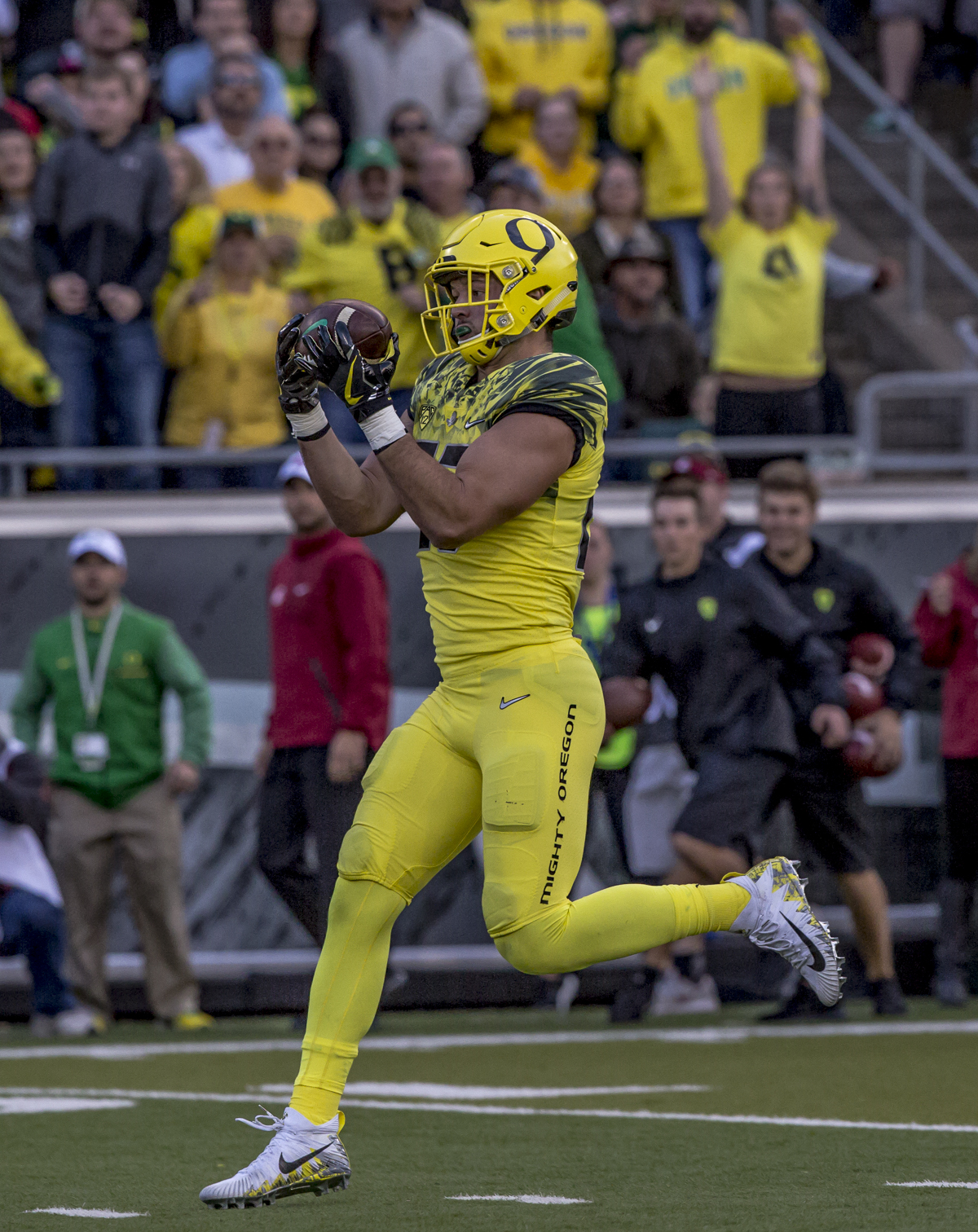 Oregon tight end Jacob Breeland (#27) catches a pass from Oregon quarterback Braxton Burmeister (#11). The Oregon Ducks trail the Washington State Cougars 10 to 13 at the end of the first half. Photo by Ben Lonergan, Oregon News Lab