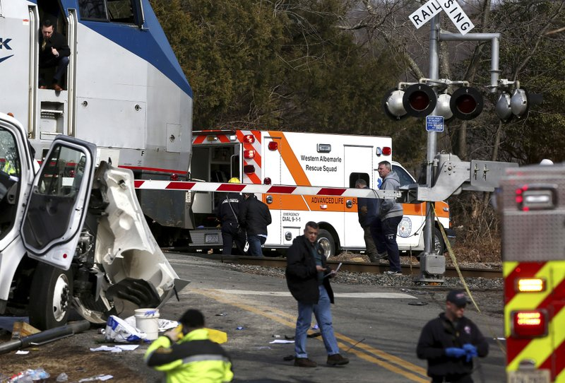 <p>The railroad crossing arm is seen lowered next to the scene of where an Amtrak train carrying multiple Republican lawmakers crashed into a garbage truck in Crozet, Va., on Wednesday, Jan. 31, 2018. A chartered train carrying dozens of GOP lawmakers to a Republican policy retreat in West Virginia struck a garbage truck in a rural Virginia town Wednesday. (Zack Wajsgras/The Daily Progress via AP)</p>