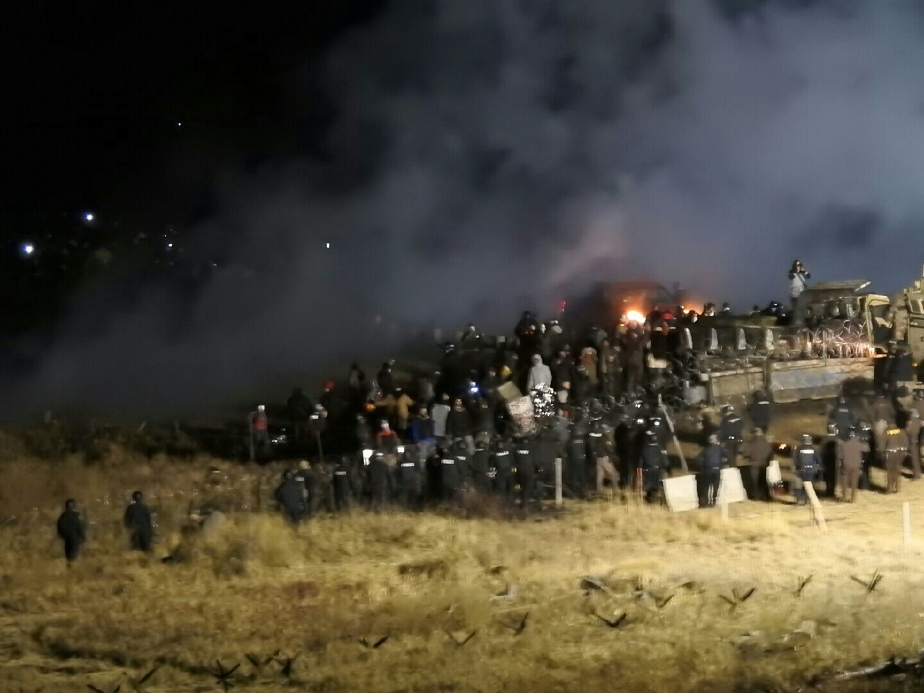 In this image provided by Morton County Sheriff's Department, law enforcement and protesters clash near the site of the Dakota Access pipeline on Sunday, Nov. 20, 2016, in Cannon Ball, N.D. At least one person arrested as protesters sought to push past a bridge on a state highway that had been blockaded since late October. (Morton County Sheriff's Department via AP)