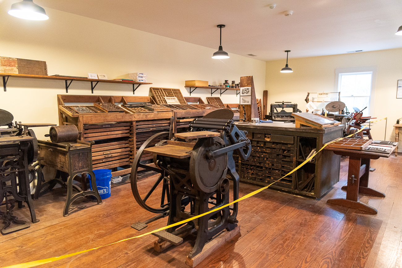 The Schram Print Shop, a newer building made to replicate an old building, is filled with old printing press artifacts and machinery.{ }/ Image: Phil Armstrong, Cincinnati Refined // Published: 12.5.19