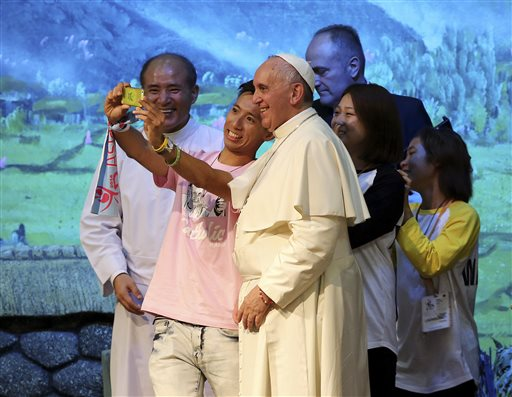 Pope Francis poses for a selfie with young participants during a meeting with Asian youth at the Solmoe Sanctuary in Dangjin, South Korea.