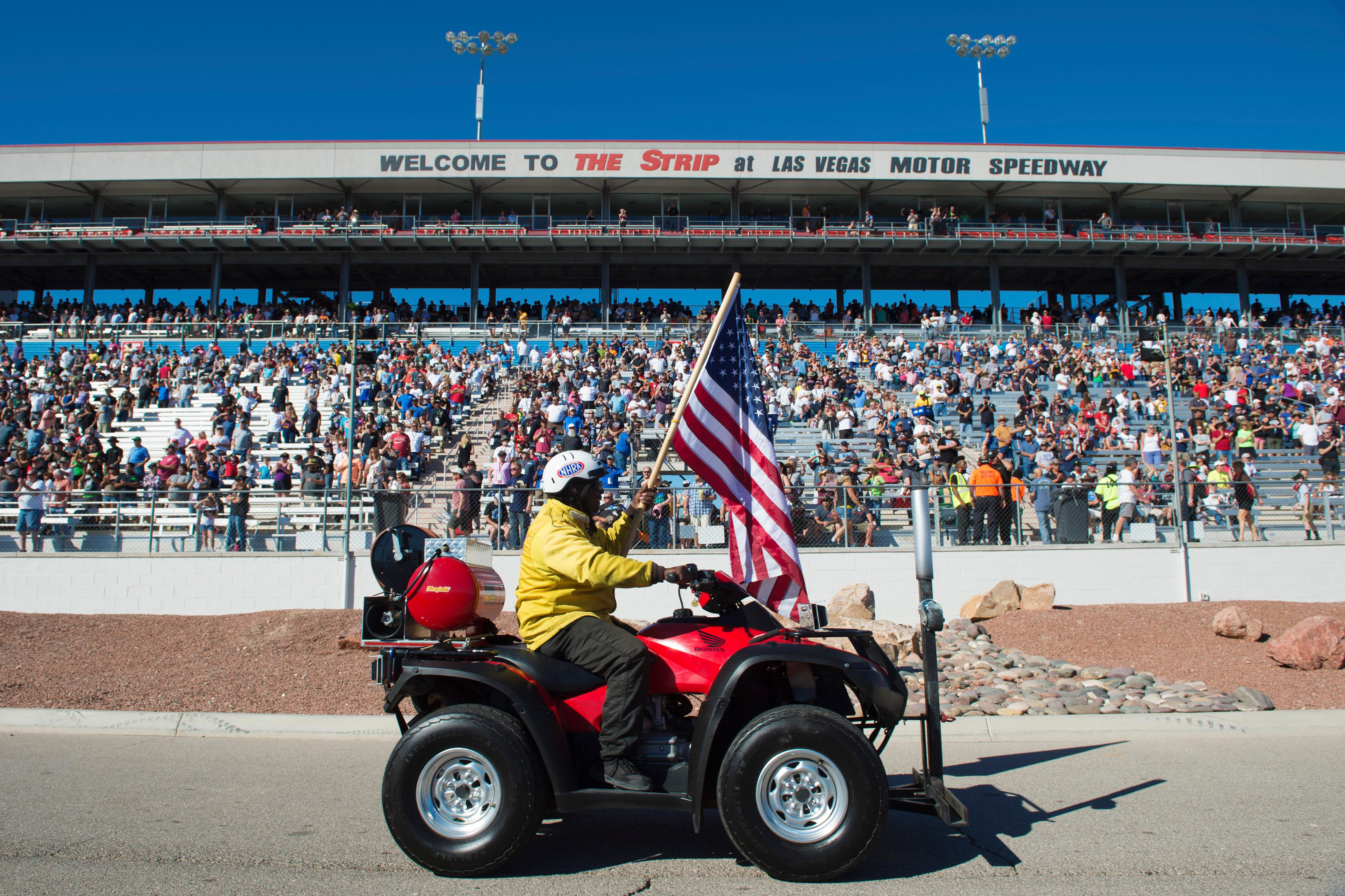 A safety official carries a flag on the return lane before the NHRA Toyota Nationals Sunday, October 29, 2017, at The Strip at the Las Vegas Motor Speedway. CREDIT: Sam Morris/Las Vegas News Bureau