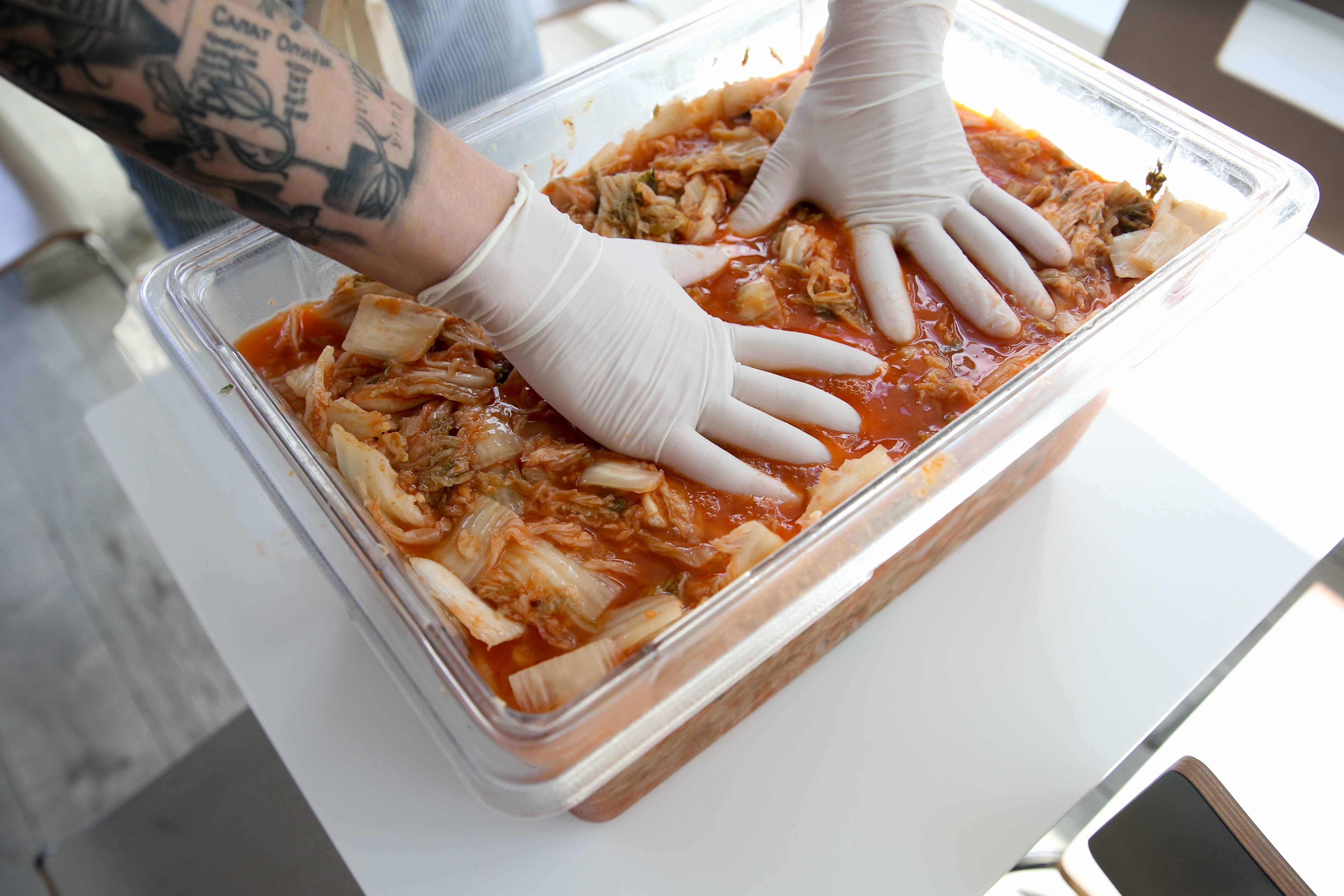 Once the leaves are coated with the spice mixture, pour the kimchi into a heavy duty plastic or glass container and keep it in a room that's 75-85 degrees Fahrenheit to allow fermentation to start. (Image: Amanda Andrade-Rhoades/ DC Refined)