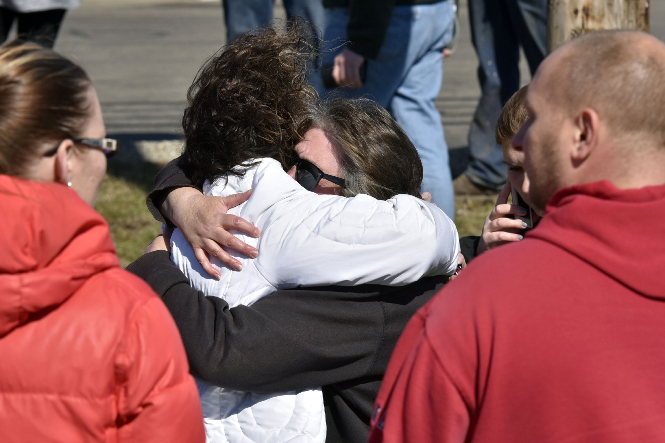 A child is comforted Monday, Feb. 29, 2016, near Middletown, Ohio after a school shooting at Madison Local Schools.  An Ohio sheriff says a 14-year-old suspect in a school shooting that wounded four classmates, including two who were shot, is in a juvenile lock-up and facing several charges. Butler County Sheriff Richard Jones says the boy has been charged with two counts of attempted murder, two counts of felonious assault, inducing panic and making terrorist threats.  (Nick Graham/Dayton Daily News via AP)