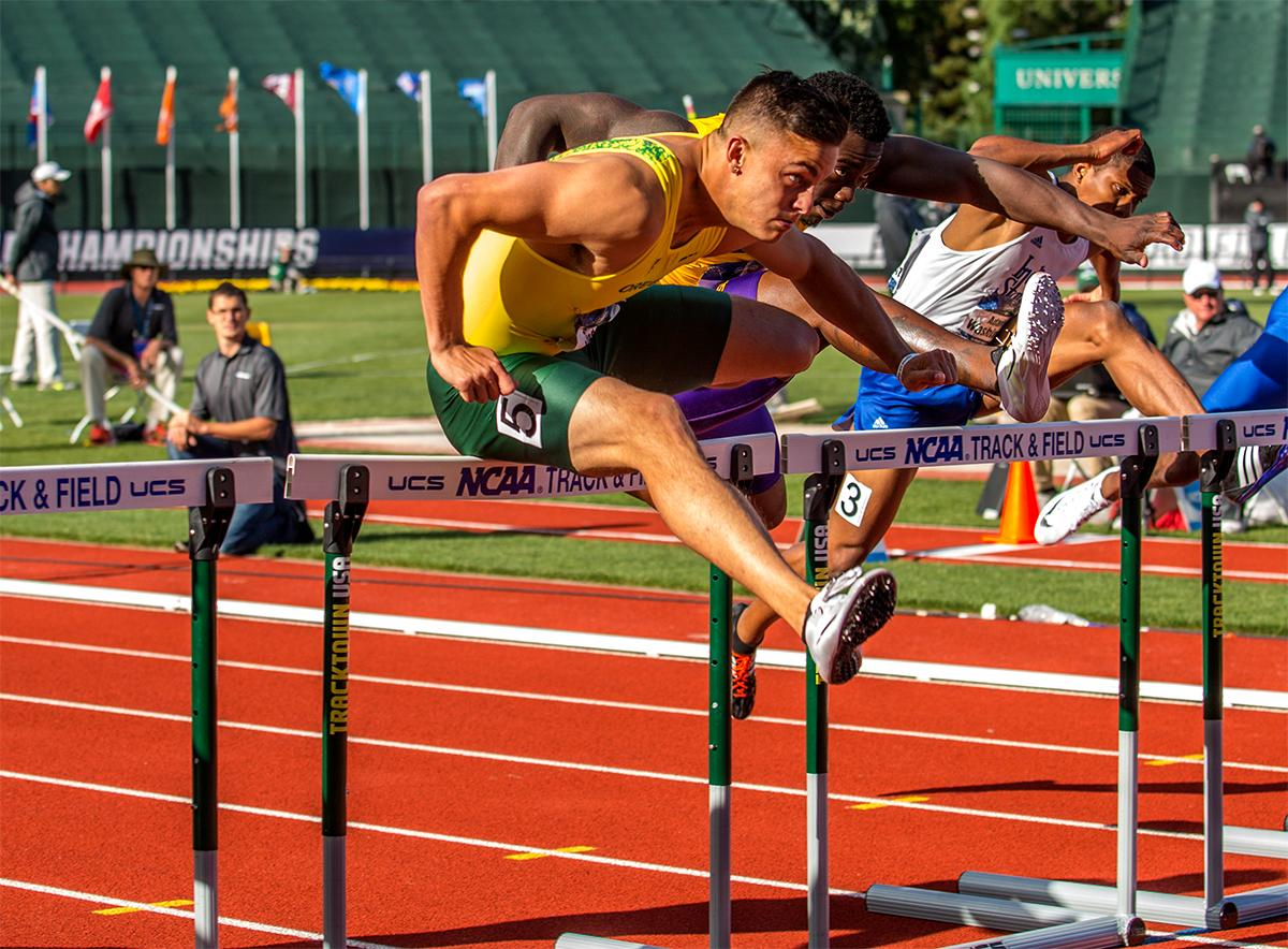 Devon Allen leaps hurdles in the 110 meters on his way to victory. Allen won the race in 13.50.  Photo by August Frank, Oregon News Lab