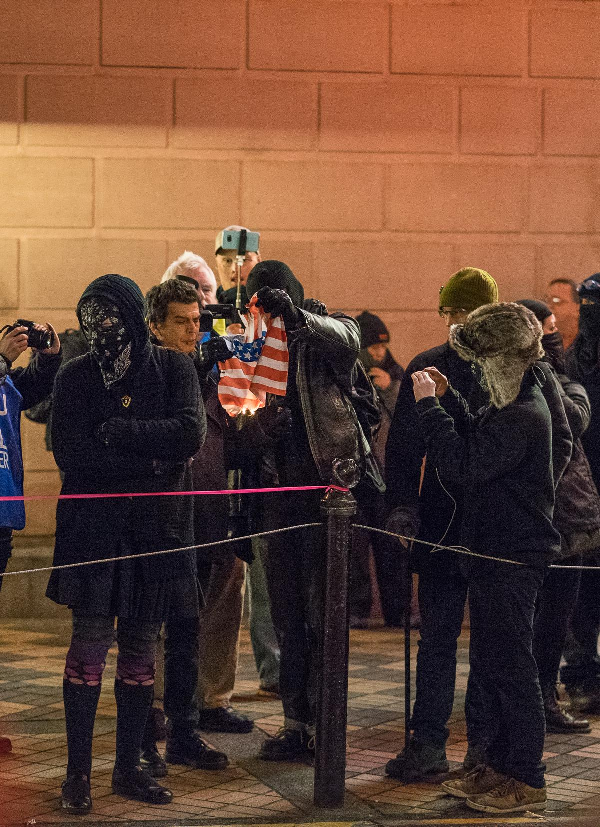 Antifa counter-protesters attempt to ignite an American flag. The alt-right group Patriot Prayer protested Hillary Clinton's Portland speaking engagement outside the Arlene Schnitzer Concert Hall on Tuesday, December 12. Their demonstration was met with a counter-protest by Antifa, and the two groups traded insults and jeers across SW Main Street from 6:00 p.m. until the event's conclusion at approximately 9:30 p.m. Throughout the evening, both Patriot Prayer and Antifa sporadically marched around the theater. At least one scuffle occurred during one such march. Photo by Kit MacAvoy, Oregon News Lab