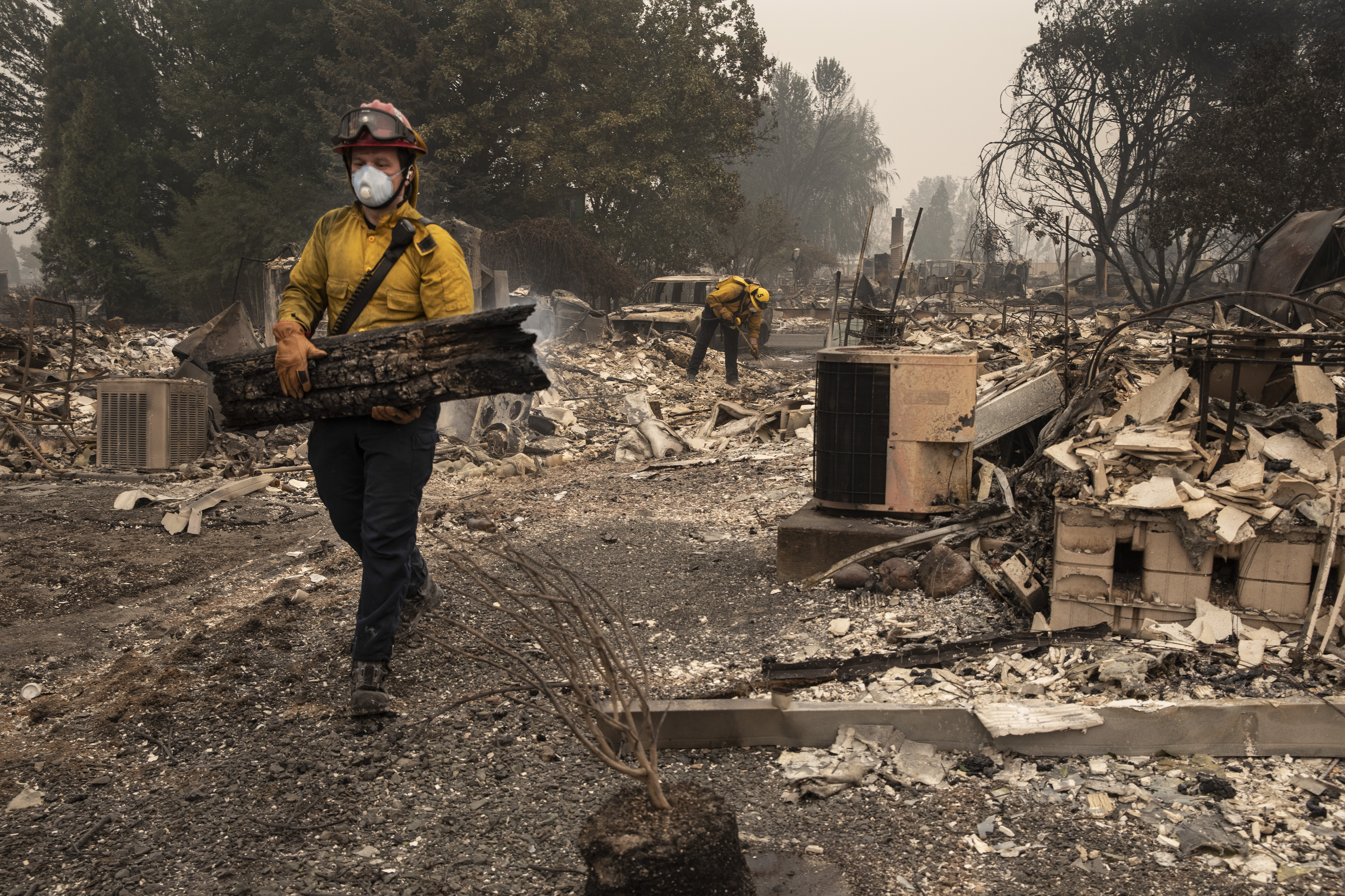 Jackson County District 5 firefighter Captain Aaron Bustard works on a smoldering fire in a burned neighborhood in Talent, Ore., Friday, Sept. 11, 2020, as destructive wildfires devastate the region. (AP Photo/Paula Bronstein)