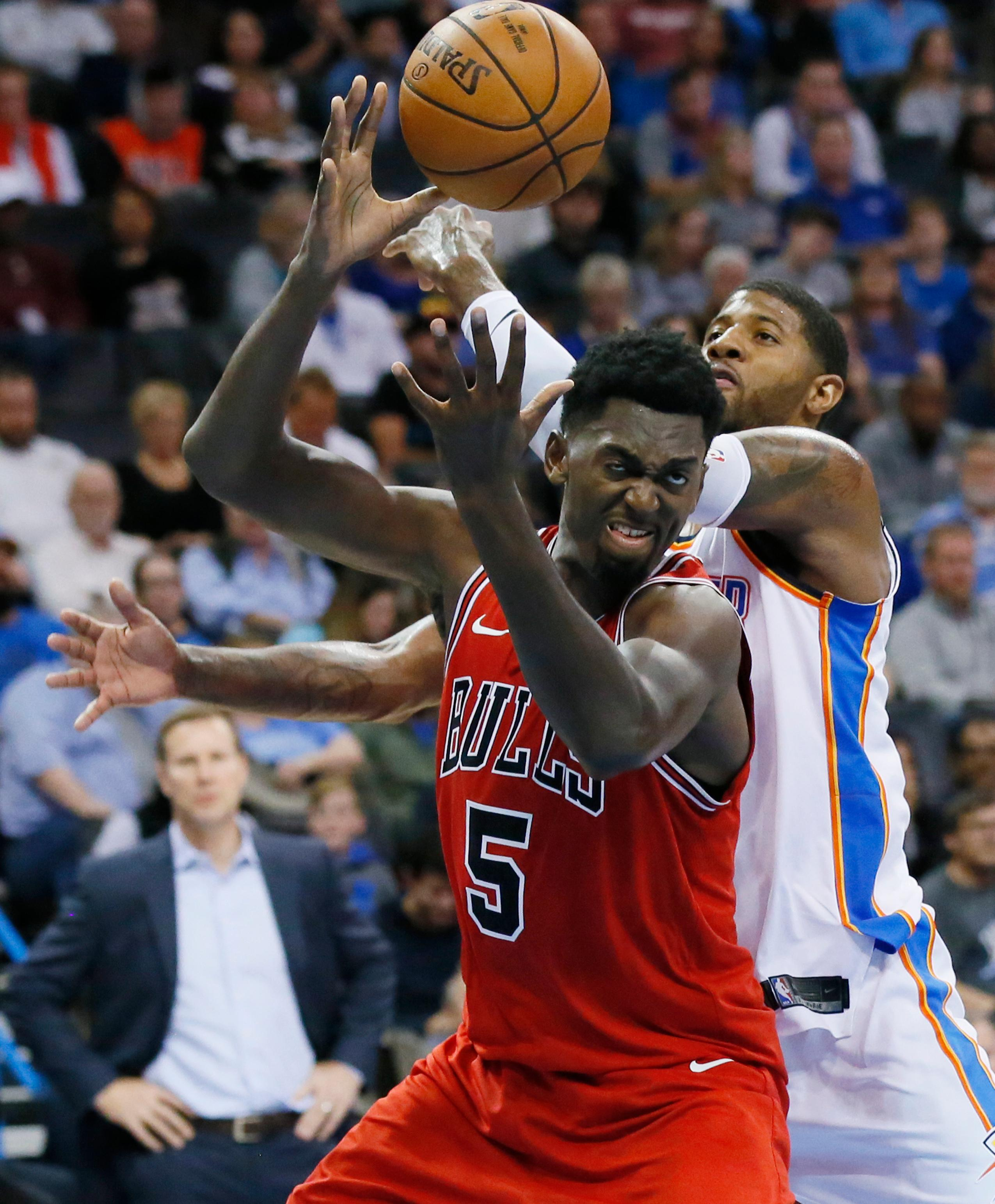 Chicago Bulls forward Bobby Portis (5) grabs a rebound in front of Oklahoma City Thunder forward Paul George, right, in the second quarter of an NBA basketball game in Oklahoma City, Wednesday, Nov. 15, 2017. (AP Photo/Sue Ogrocki)