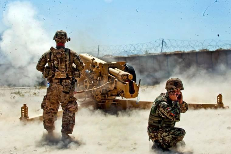 A U.S. soldier observes the firing of a D-30 122mm howitzer by Afghan soldiers during certification exercises on Forward Operating Base Tagab in Kapisa province, Afghanistan, Sept. 5, 2013.