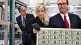 Mnuchin shows off a sheet of new $1 bills, first with his signature