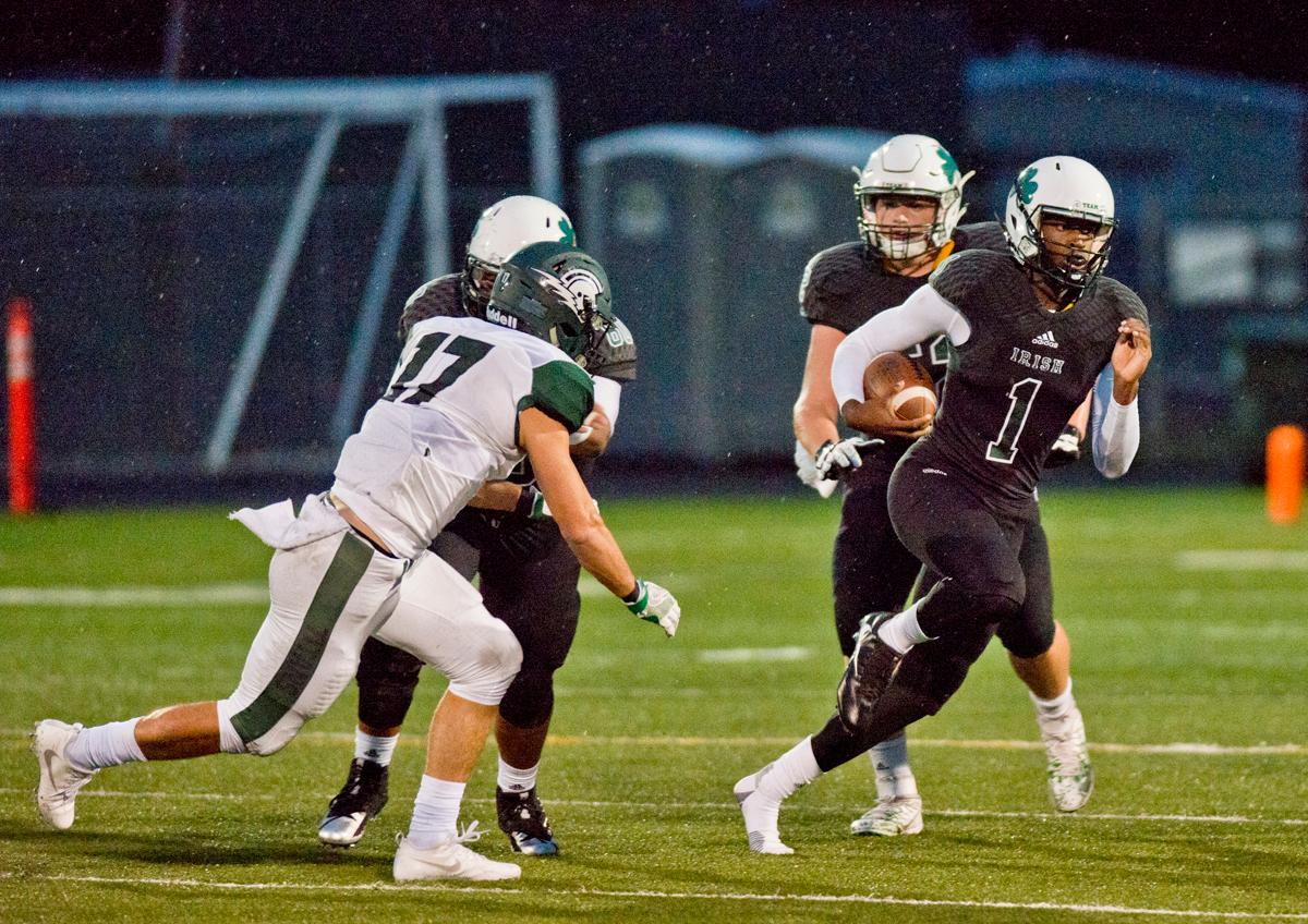 Sheldon Irish quarterback Michael Johnson (#1) scrambles to evade West Salem Titans linebacker Micah Pugh (#17). On a rainy Monday evening Sheldon defeated West Salem 41-7. The game had been postponed from Friday due to unhealthy levels of smoke in the atmosphere due to nearby forest fires. Photo by Dan Morrison, Oregon News Lab