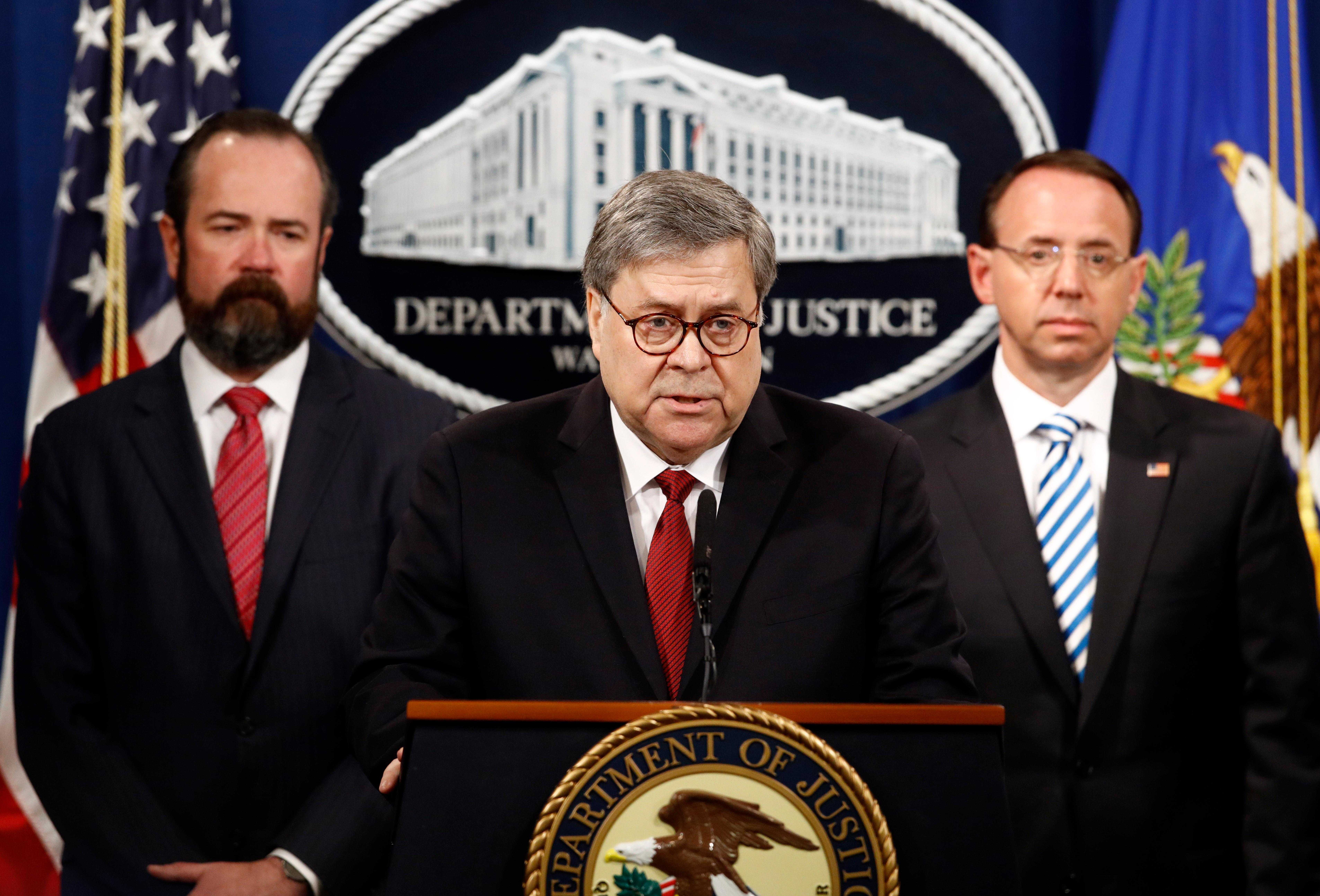 Attorney General William Barr speaks alongside Deputy Attorney General Rod Rosenstein, right, and acting Principal Associate Deputy Attorney General Edward O'Callaghan, left, about the release of a redacted version of special counsel Robert Mueller's report during a news conference, Thursday, April 18, 2019, at the Department of Justice in Washington. (AP Photo/Patrick Semansky)