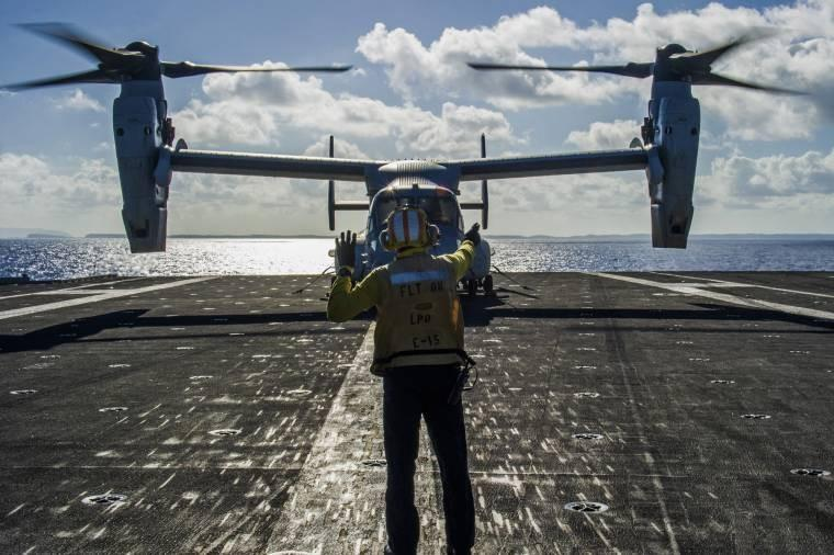 Navy Petty Officer 1st Class Kerry Carter signals the pilot of a Marine Corps MV-22 Osprey in the Philippine Sea, before crews load supplies on it during Operation Damayan, an effort to help the Philippine government in aftermath of Typhoon Haiyan.