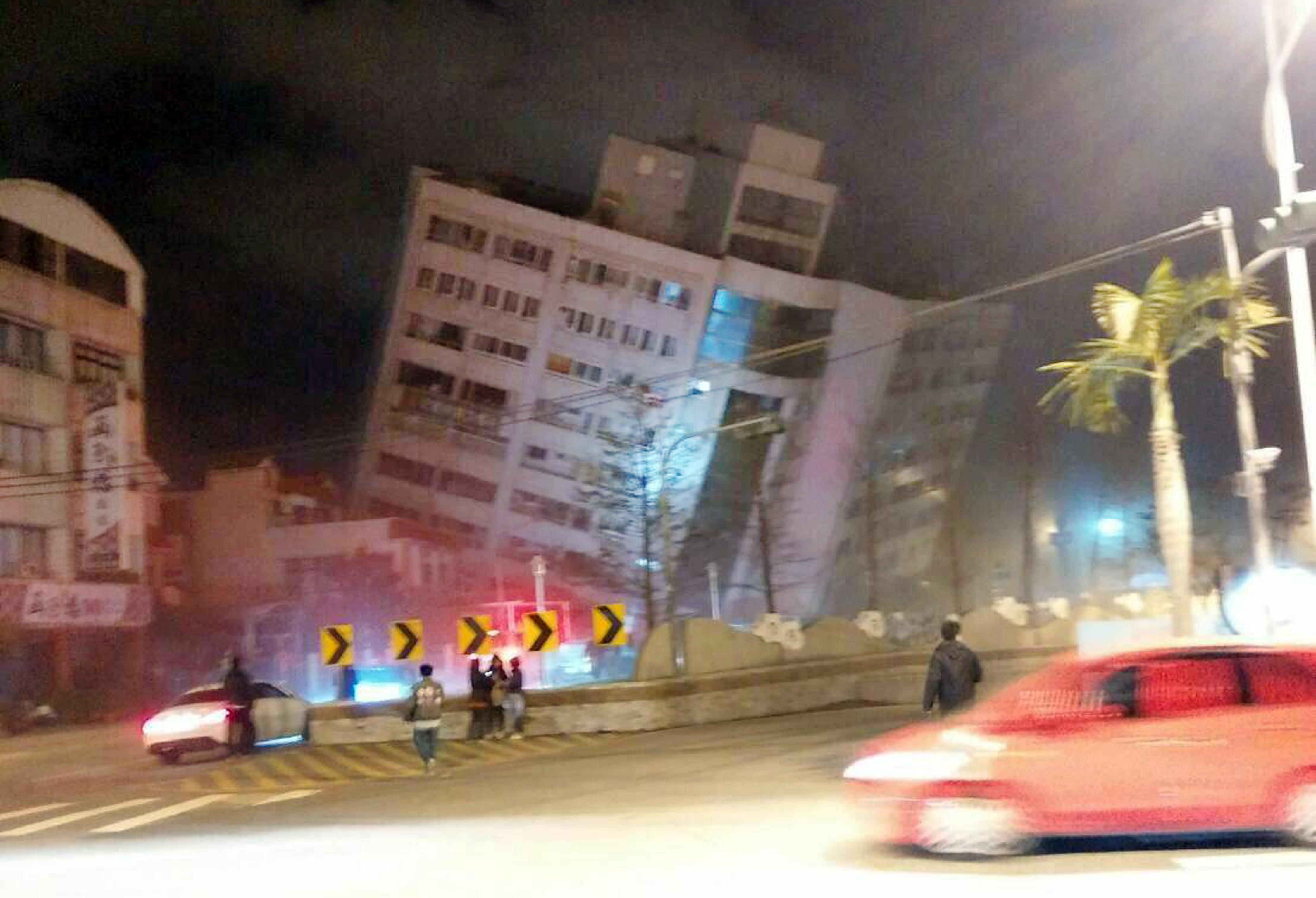 In this photo released by Hualien County Fire Bureau, rescuers are seen entering an building that collapsed onto its side from an early morning earthquake in Hualien County, eastern Taiwan, Wednesday, Feb. 7 2018. A 6.4-magnitude earthquake has struck eastern Taiwan, according to the U.S. Geological Survey. (Hualien County Fire Bureau via AP)