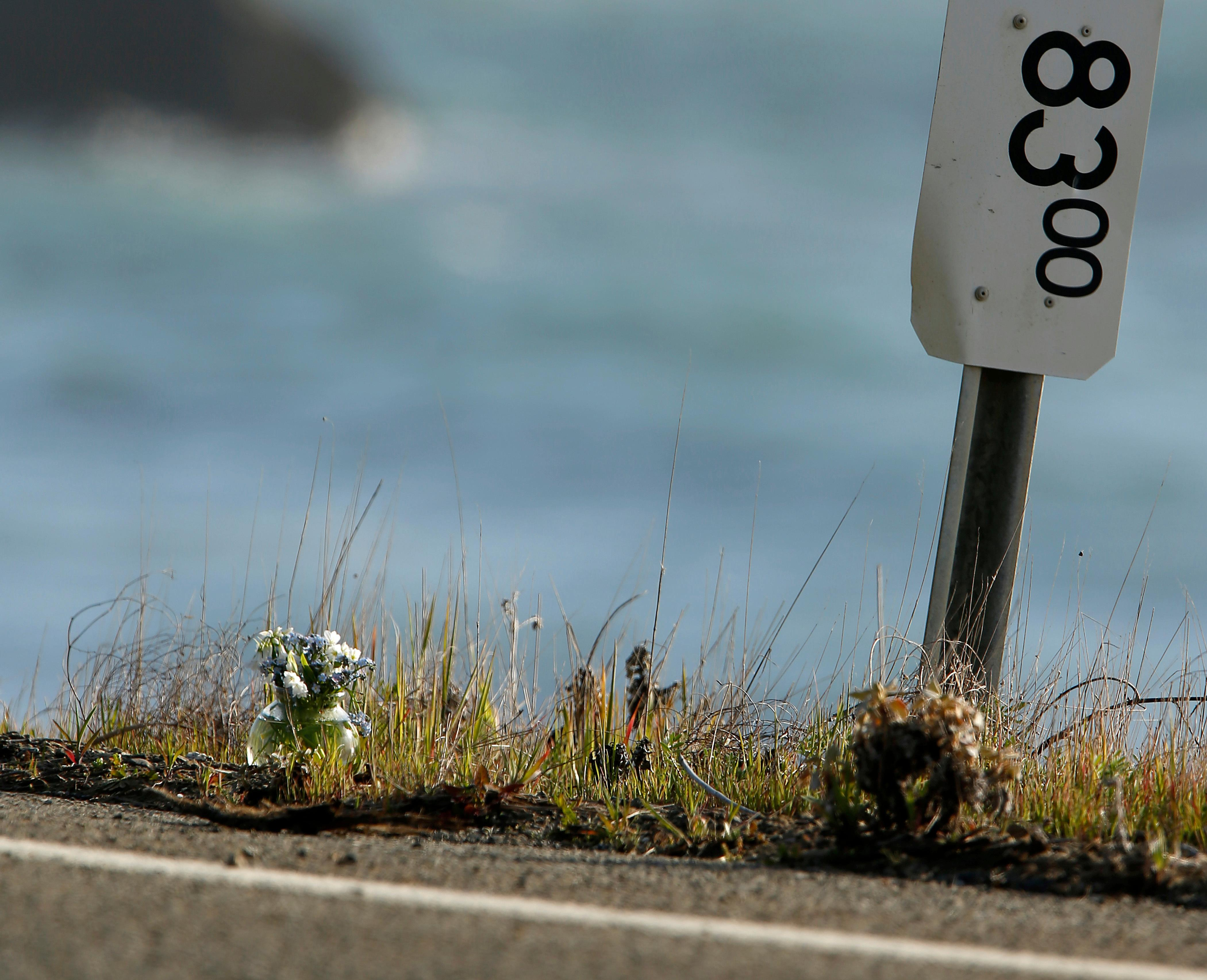 A small vase of flowers, at left, sits beside a mile marker Wednesday, March 28, 2018, near the pullout where the SUV of Jennifer and Sarah Hart was recovered off the Pacific Coast Highway near Westport, Calif. The bodies of the two women and three of their adopted children were recovered after the vehicle plunged over the cliff two days earlier, while three more of their children, Devonte Hart, 15, Hannah Hart, 16, and Sierra Hart, 12, have not been found. (Alvin Jornada/The Press Democrat via AP)