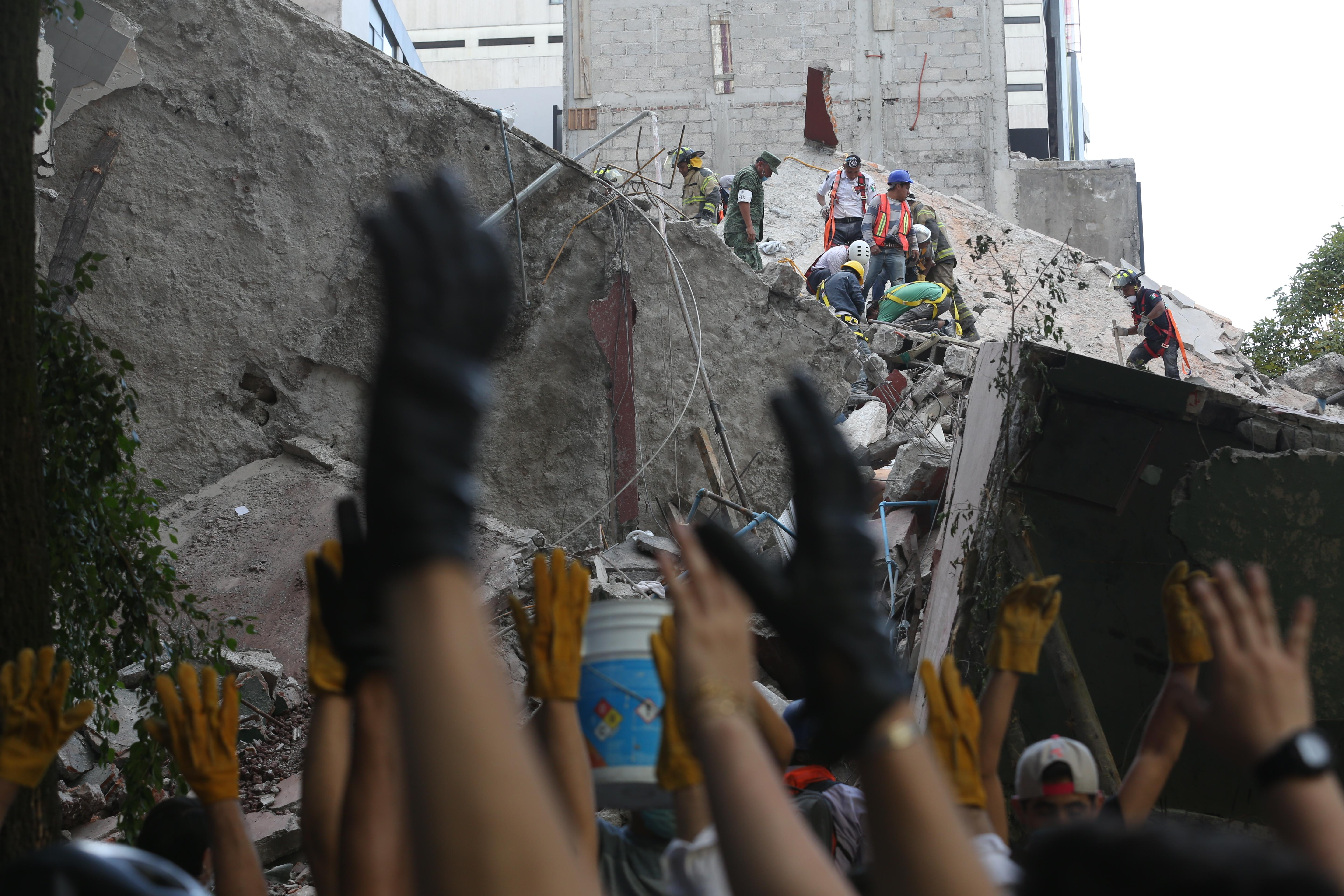 First responders raise their hands asking for silence as they work on removing the rubble of a collapsed building looking for survivors trapped underneath, after a 7.1 earthquake in Mexico City, Tuesday, Sept. 19, 2017.  The earthquake stunned central Mexico, killing more than 100 people as buildings collapsed in plumes of dust.  (AP Photo/Gustavo Martinez Contreras)