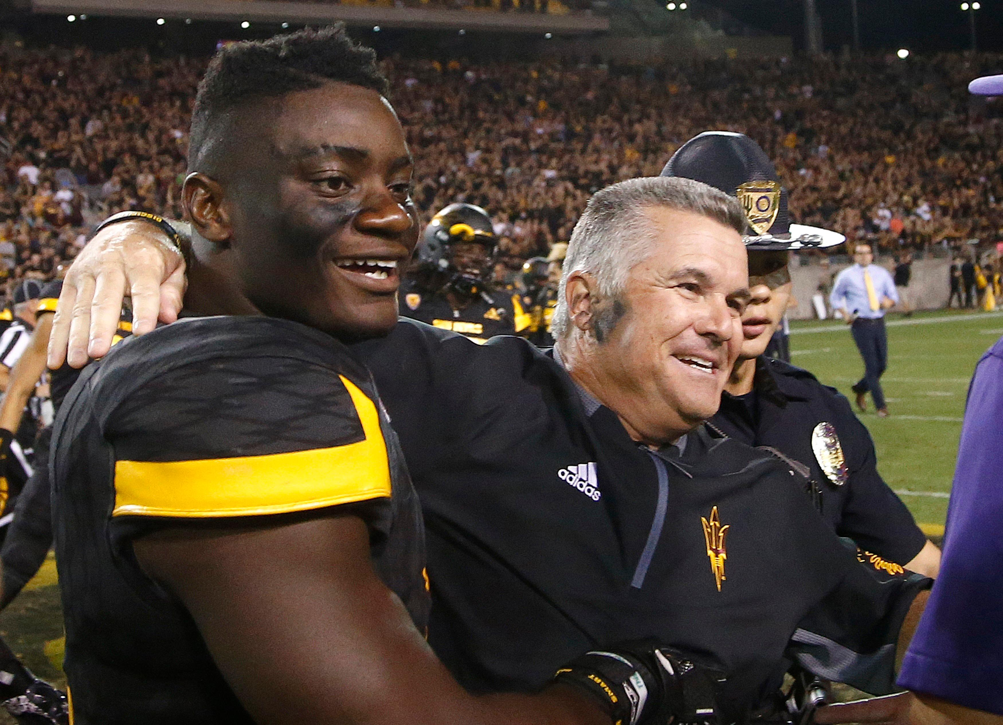 FILE - In this Oct. 14, 2017, file photo, Arizona State head coach Todd Graham, right, celebrates with linebacker Christian Sam, left, after an NCAA college football game against Washington, in Tempe, Ariz. Sam was selected to the AP All-Conference Pac-12 team announced Thursday, Dec. 7, 2017. (AP Photo/Ross D. Franklin, File)