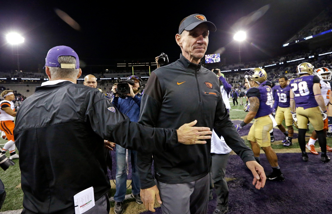 Washington head coach Chris Petersen, left, gives Oregon State head coach Gary Andersen a pat after they greeted each other at the end of an NCAA college football game Saturday, Oct. 22, 2016, in Seattle. Washington won 41-17. (AP Photo/Elaine Thompson)