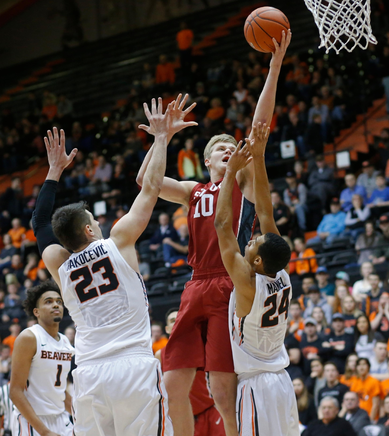 Stanford's Michael Humphrey (10) shoots over Oregon State's Gligorije Rakocevic (23) and Kendal Manuel (24) during the first half of an NCAA college basketball game in Corvallis, Ore., Thursday, Jan. 19, 2017. (AP Photo/Timothy J. Gonzalez)