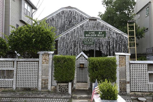 The beer can house sits between newer homes in Houston. Former owner John Milkovisch covered the outside on the house with siding made of cut and flatten beer cans and garlands made from the lids.