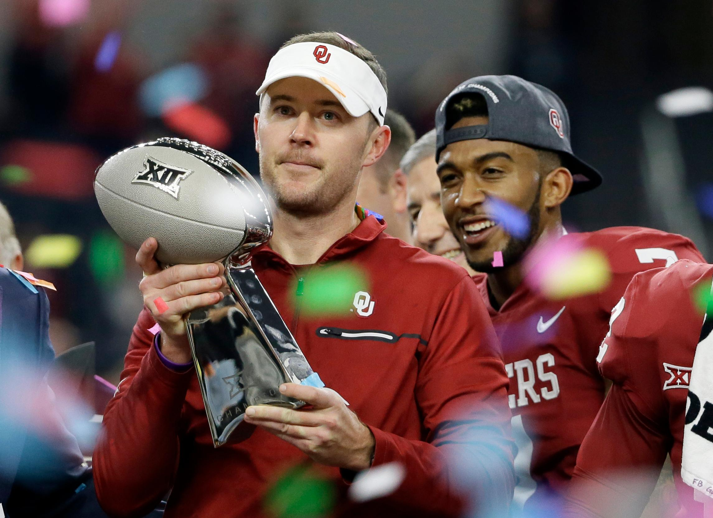Oklahoma head coach Lincoln Riley holds the Big 12 Conference championship NCAA college football game trophy after Oklahoma defeated TCU on Saturday, Dec. 2, 2017, in Arlington, Texas. (AP Photo/Tony Gutierrez)