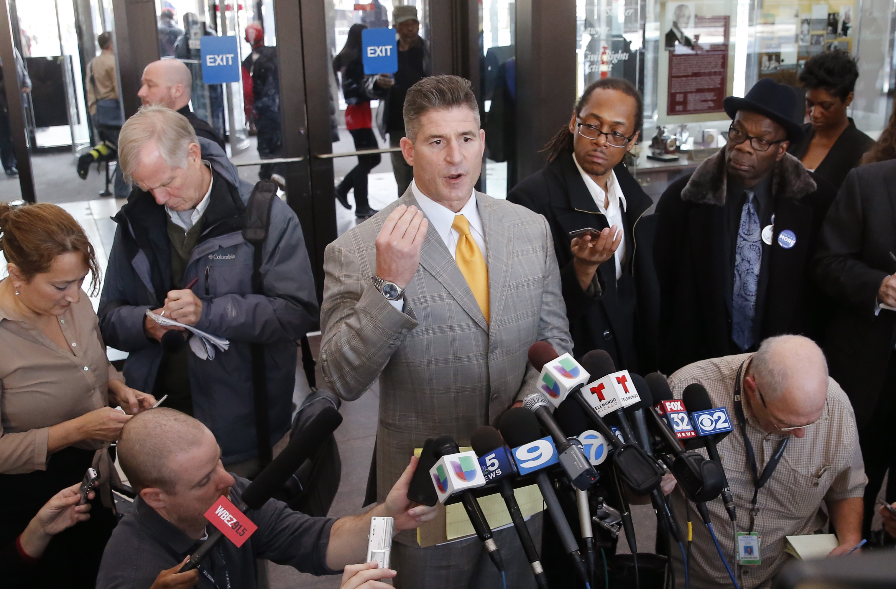 Attorney Daniel Herbert, center, talks to reporters after the bond hearing for his client, Chicago police officer Jason Van Dyke, on murder charges in the killing of 17-year-old Laquan McDonald, Tuesday, Nov. 24, 2015, in Chicago. Van Dyke's hearing is just a day ahead of a deadline for the city to release a squad-car video of the shooting. (AP Photo/Charles Rex Arbogast)