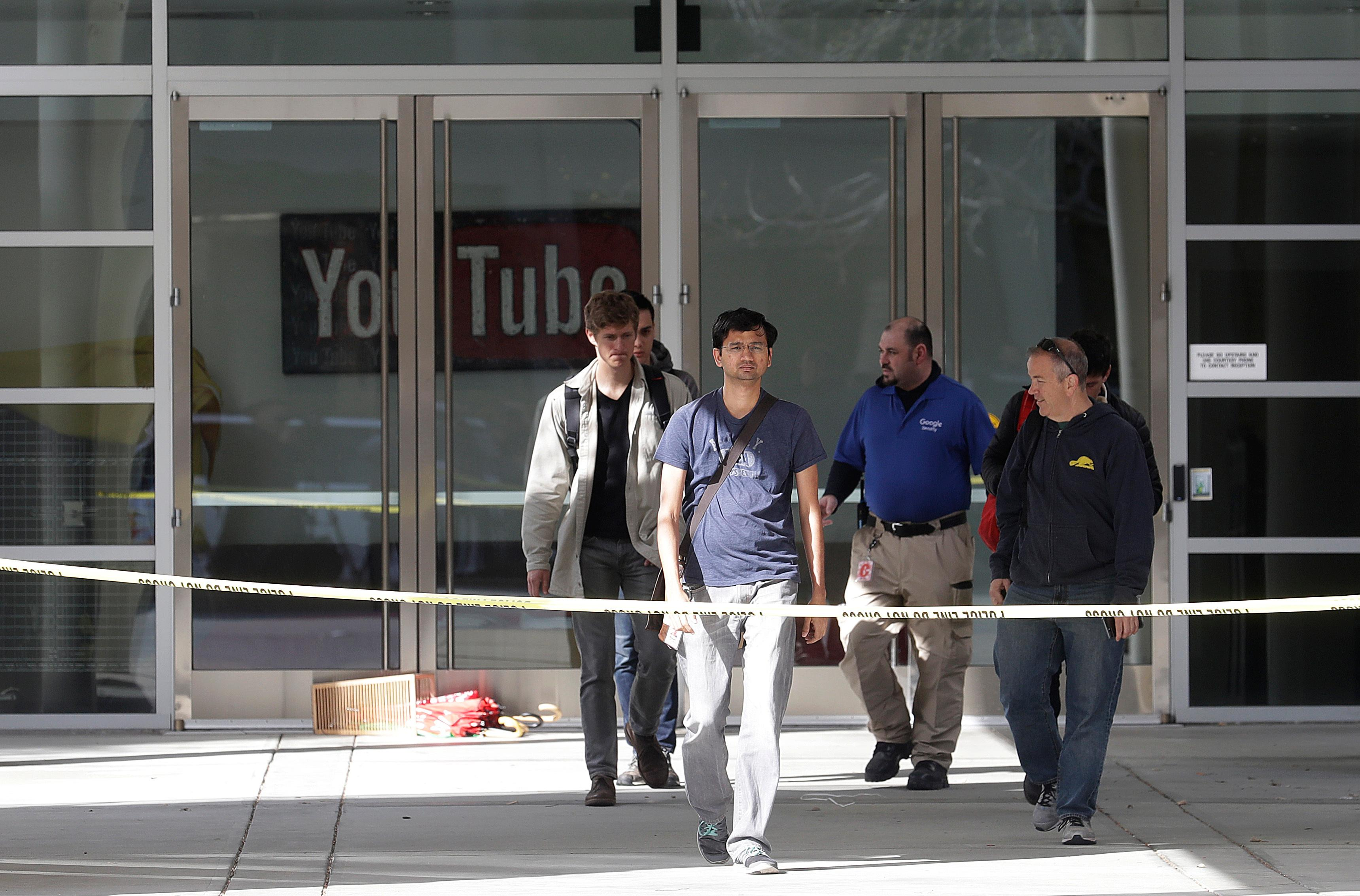 A group walks out of a YouTube office building in San Bruno, Calif., Wednesday, April 4, 2018. A woman suspected of shooting three people at YouTube headquarters before killing herself was furious with the company because it had stopped paying her for videos she posted on the platform, her father said Tuesday, April 3, 2018. (AP Photo/Jeff Chiu)
