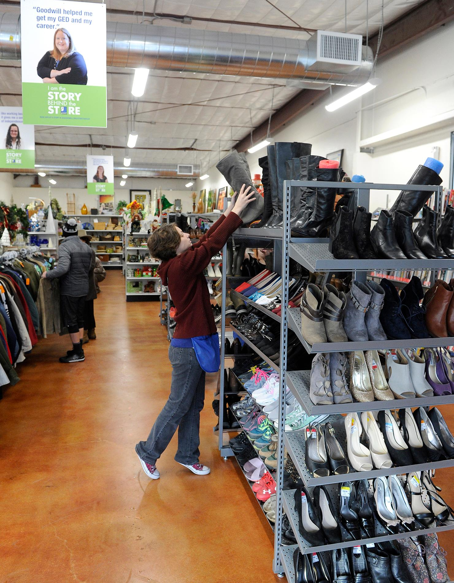 Andy Atkinson / Daily TidingsStore employee Caley Obrien organizes boots at the newly remodeled Goodwill during the reopening Friday morning.