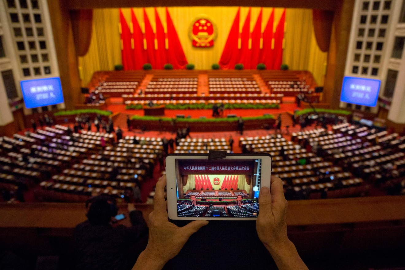 FILE - In this March 12, 2015 file photo, a delegate takes a photo before a plenary session of the National People's Congress in the Great Hall of the People in Beijing. Democracy Chinese-style will go on display when the country's rubberstamp legislature, the National People's Congress opens its annual sessions in Beijing on Sunday, March 5, 2017. (AP Photo/Ng Han Guan, File)