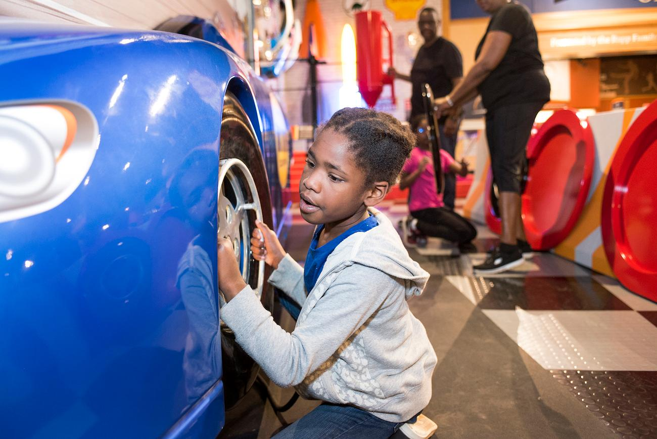 In the Church Brothers Collision Repair Motorsports Garage, a girl tests her speed (and safety) in a pit-stop challenge. Nearby is an Indy 500 race car and track tables to race others. / Image courtesy of Children's Museum of Indianapolis // Published: 4.2.19