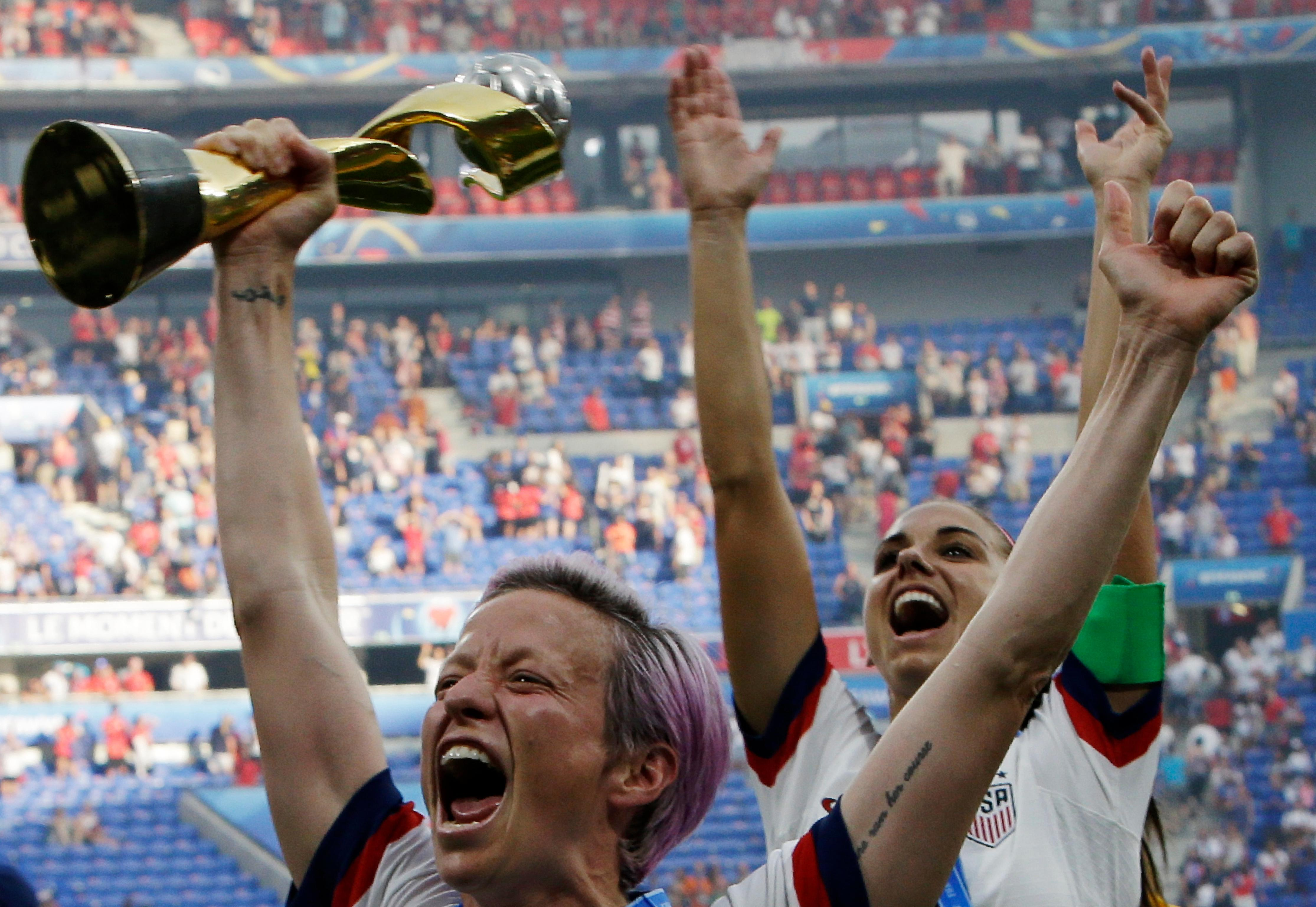 United States' Megan Rapinoe, left, and Alex Morgan celebrate with the trophy after winning the Women's World Cup final soccer match between US and The Netherlands at the Stade de Lyon in Decines, outside Lyon, France, Sunday, July 7, 2019. (AP Photo/Claude Paris)