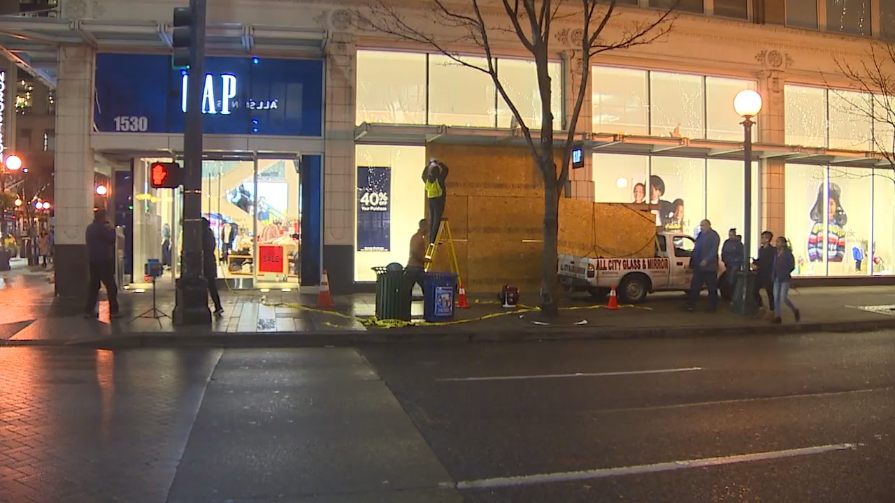 Workers repair windows after a van crashed through the front of the Gap store in Downtown Seattle. (Photo: KOMO News)