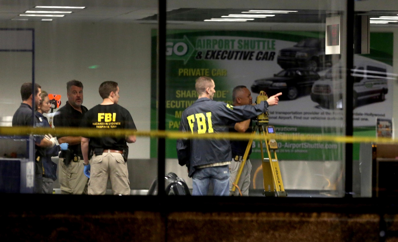 Investigators work in Terminal 2 at Ft. Lauderdale-Hollywood International Airport, Saturday, Jan. 7, 2017,  the day after a shooting in the baggage area.  Authorities say Army veteran Esteban Santiago of Anchorage, Alaska, drew a gun from his checked luggage on arrival and opened fire on fellow travelers.   (Mike Stocker/South Florida Sun-Sentinel via AP)