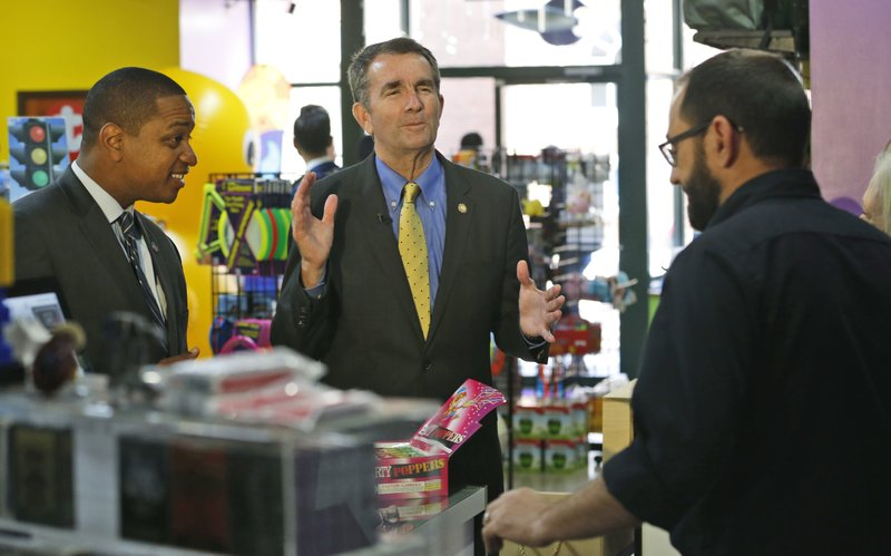 Democratic gubernatorial candidate Lt. Governor Ralph Northam, center, and Democratic Lt. Gov. candidate Justin Fairfax, left, visit business owners at a store in Winchester, Va., Wednesday Oct. 25, 2017.{&amp;nbsp;}Northam may have a politician's dream background, but he's still struggling with how to define himself in the age of Trump. (AP Photo/Steve Helber) <p></p>