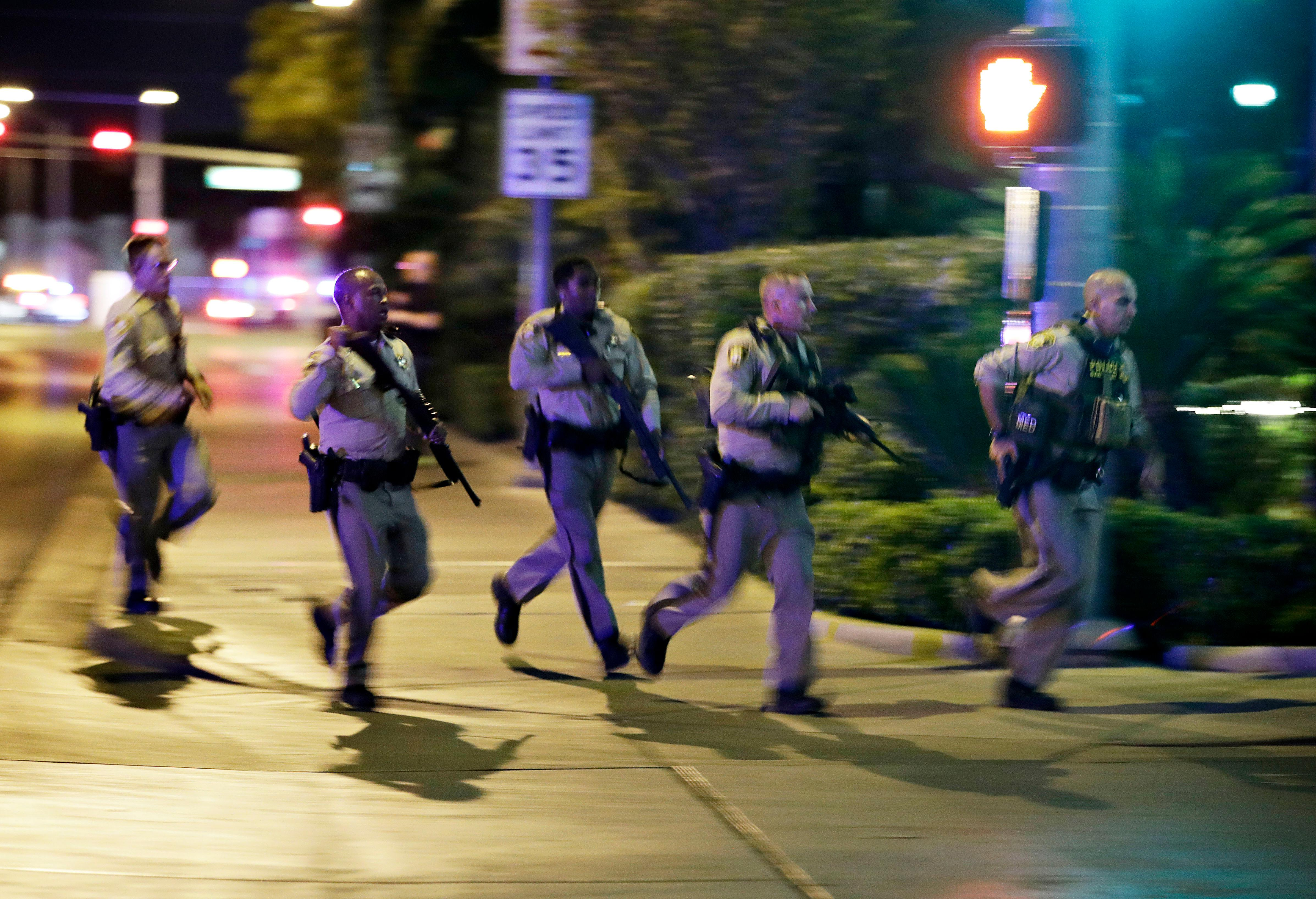 Police run to cover at the scene of a shooting near the Mandalay Bay resort and casino on the Las Vegas Strip, Sunday, Oct. 1, 2017, in Las Vegas. Multiple victims were being transported to hospitals after a shooting late Sunday at a music festival on the Las Vegas Strip. (AP Photo/John Locher)