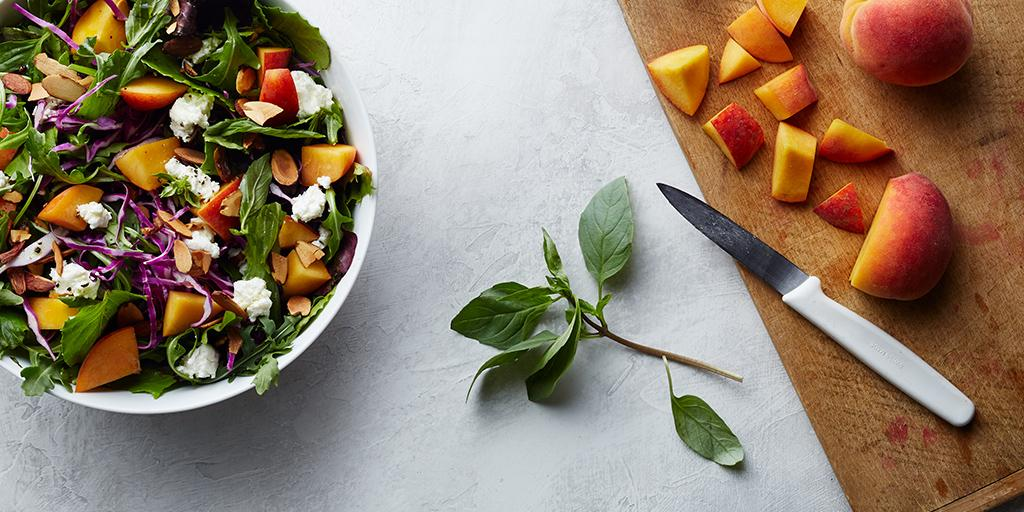 The Peach + Goat Cheese salad is far from basic, featuring organic mesclun, local peaches, goat cheese, roasted almonds, basil, balsamic vinaigrette. (Image: Courtesy sweetgreen)