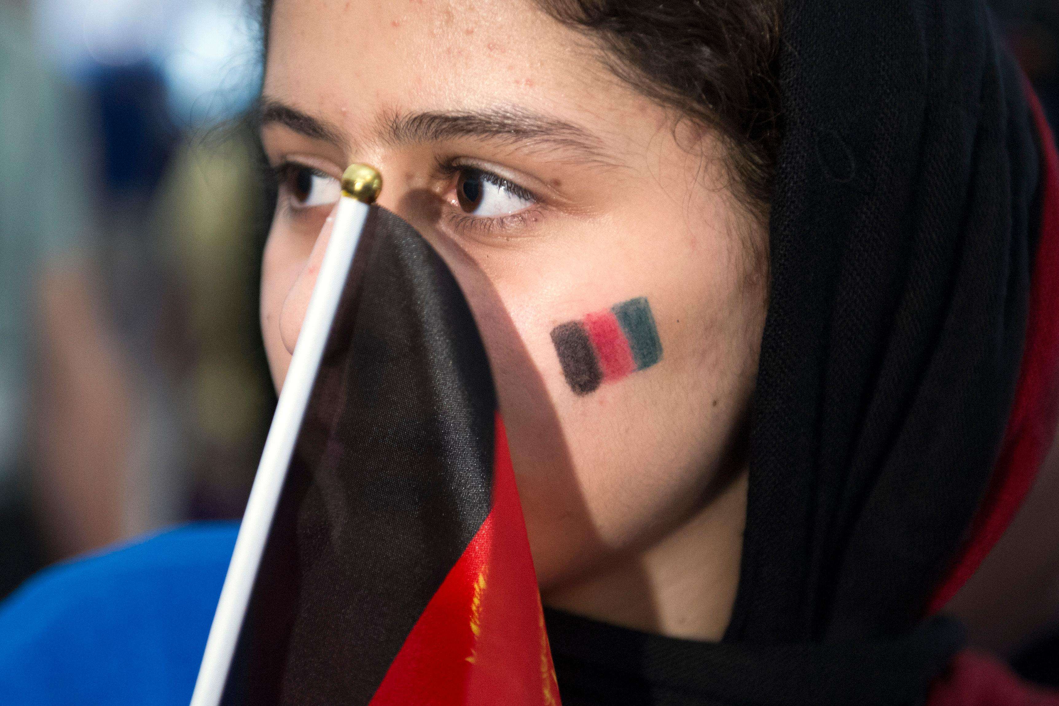 Afghanistan team member Kwasar Rashan holds the Afghan flag while waiting for the opening ceremony march of the FIRST Global Challenge 2017, in Washington, Sunday, July 16, 2017. Twice rejected for U.S. visas, the all-girls robotics team from Afghanistan arrived in Washington early Saturday after an extraordinary, last-minute intervention by President Donald Trump. (AP Photo/Cliff Owen)