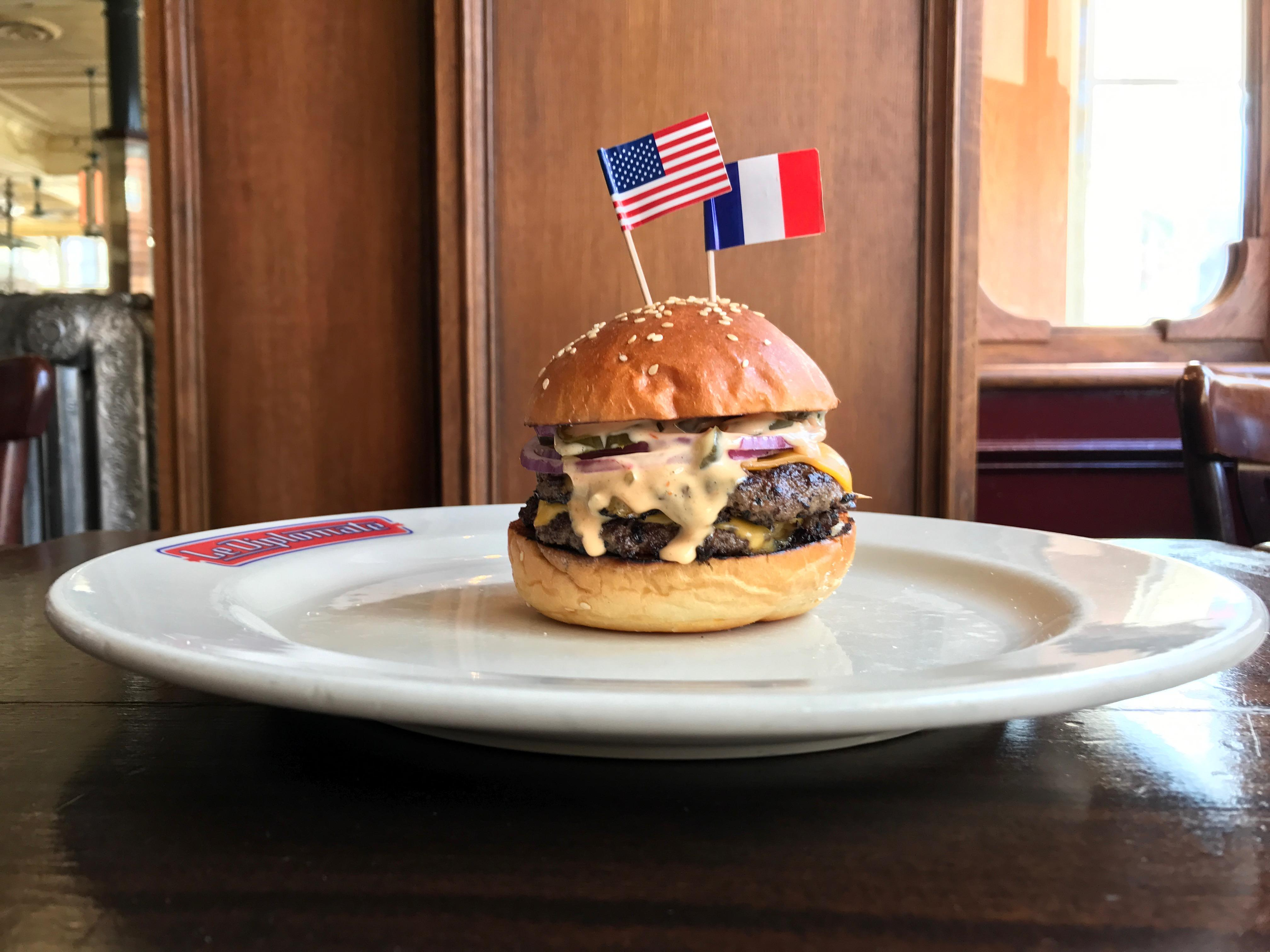 Guests feasting on the city's best French fare at Le Diplomate will also fall for their equally magnifique Burger Americain ($17). The widely-lauded hamburger features two special-blend patties topped with classic American cheese, crunchy pickles, onion, and special sauce, all on a housemade brioche bun. The menu favorite comes with a beaucoup serving of their signature pommes frites. (Photo courtesy: Le Diplomate)